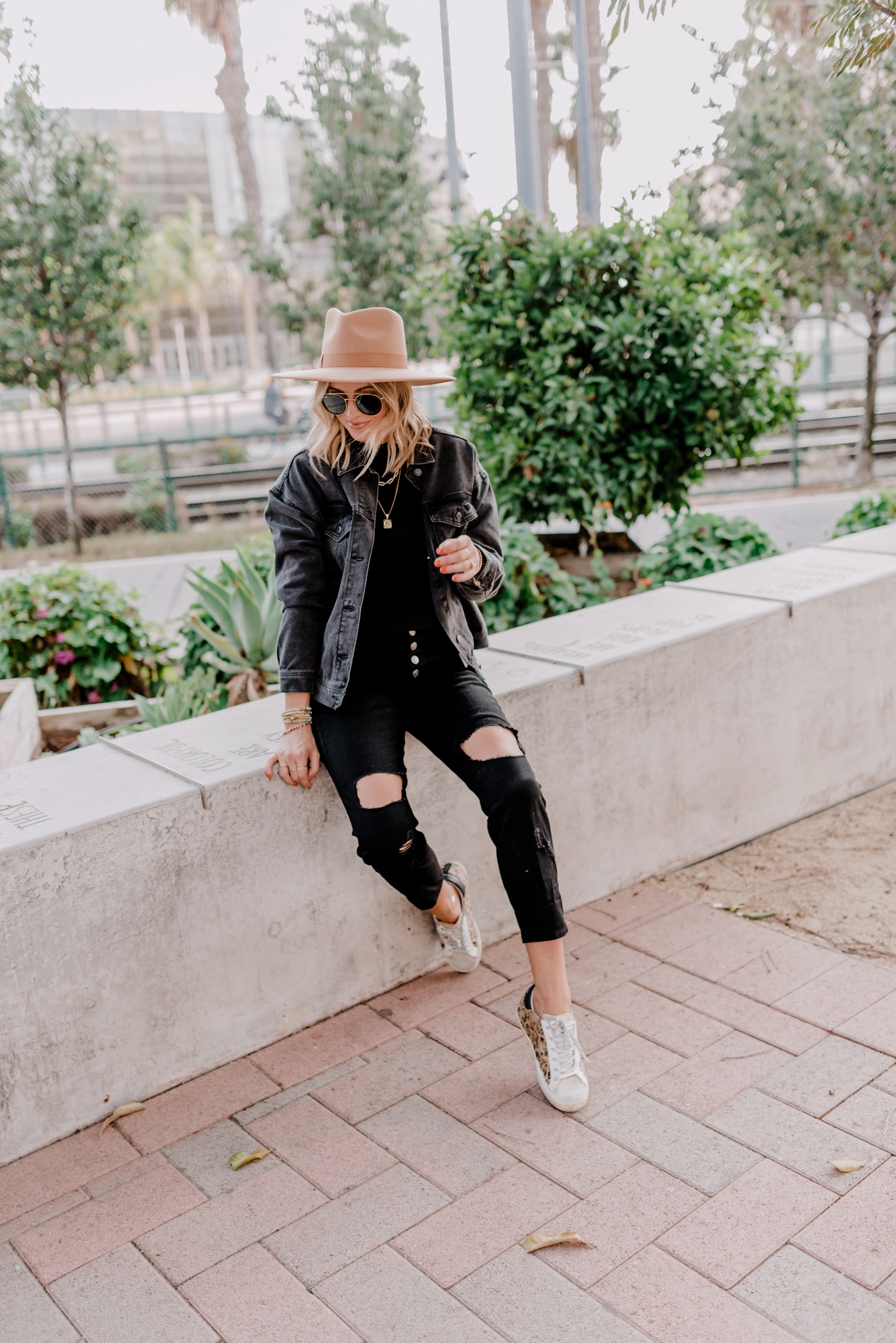 Prime Day by popular San Diego life and style blog, Navy Grace: image of a woman outside wearing a brown felt hat, black jean jacket, black shirt, black button up jeans, and Golden Goose Sneakers.