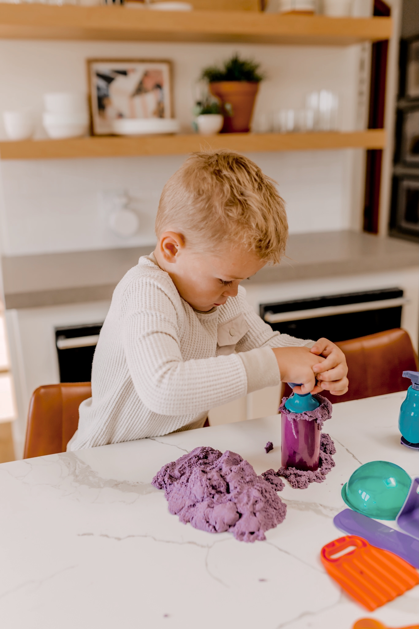 24 PRESCHOOLER GIFTS YOUR 3 TO 5 YEAR OLDS WILL LOVE featured by top San Diego lifestyle blogger, Navy Grace | Preschooler Gifts by popular San Diego lifestyle blog, Navy Grace: image of a young boy playing with kinetic sand.