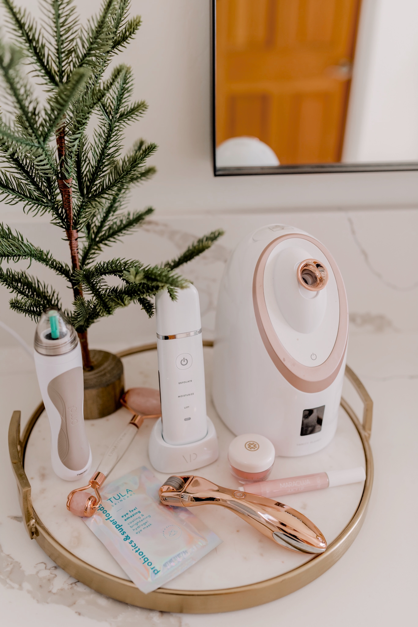 Beauty Gifts for Her by popular San Diego beauty blog, Navy Grace: image of facial steamer, microneedling tool, pmd microdermabrasion, rose quart face roller, Essia lifting wand, and Tula probiotic skincare.
