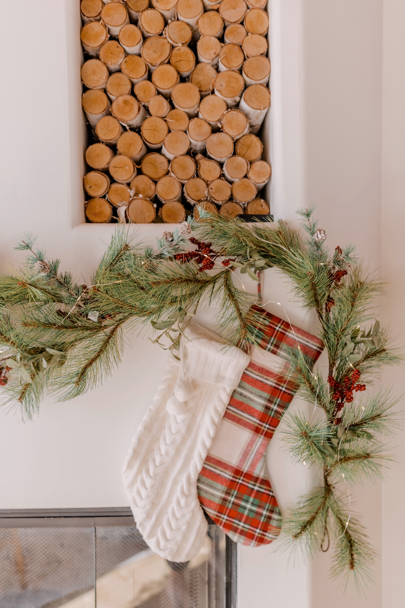 Holiday Gift Guide for the Home   Gifts for the Home by popular San Diego life and style blog, Navy Grace: image of a fireplace mantle decorated with a Christmas garland and white knit stocking and red, green and white plaid stocking.