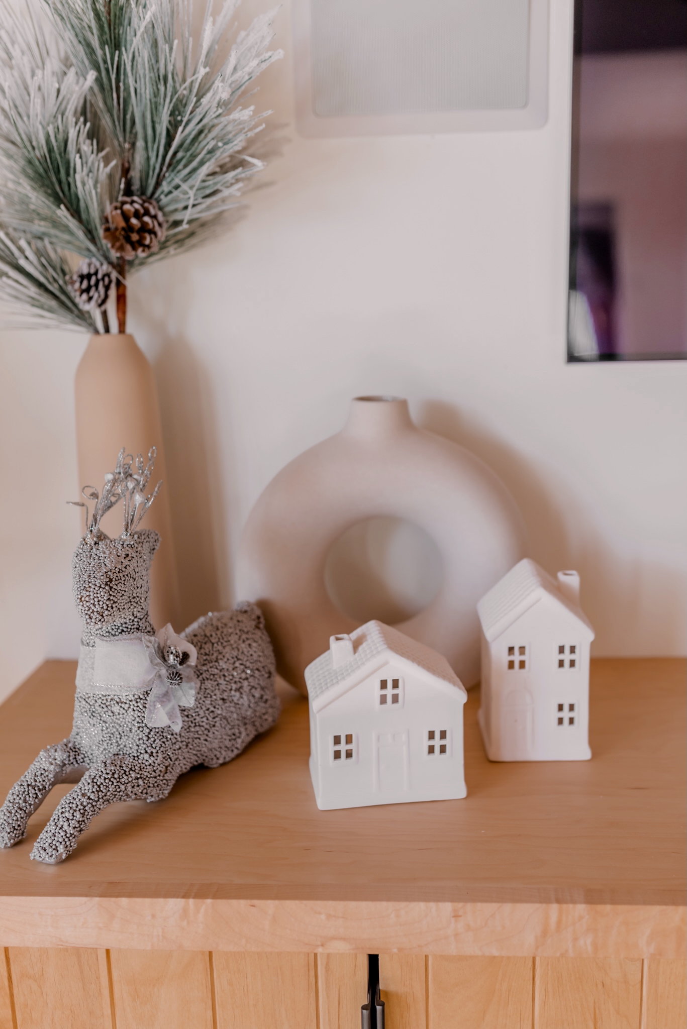 Holiday Gift Guide for the Home  Gifts for the Home by popular San Diego life and style blog, Navy Grace: image of white ceramic houses, reindeer decor, and flocked pine boughs in a cream vase.