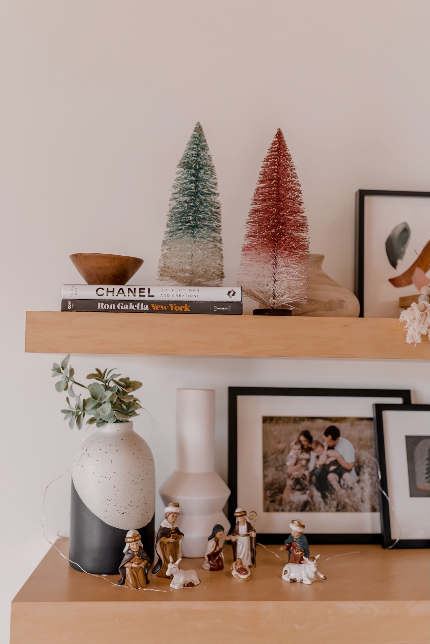 Holiday Gift Guide for the Home  Gifts for the Home by popular San Diego life and style blog, Navy Grace: image of wooden floating shelves decorated with minimalist vases, bottle brush trees, mini nativity set, and black picture frames.