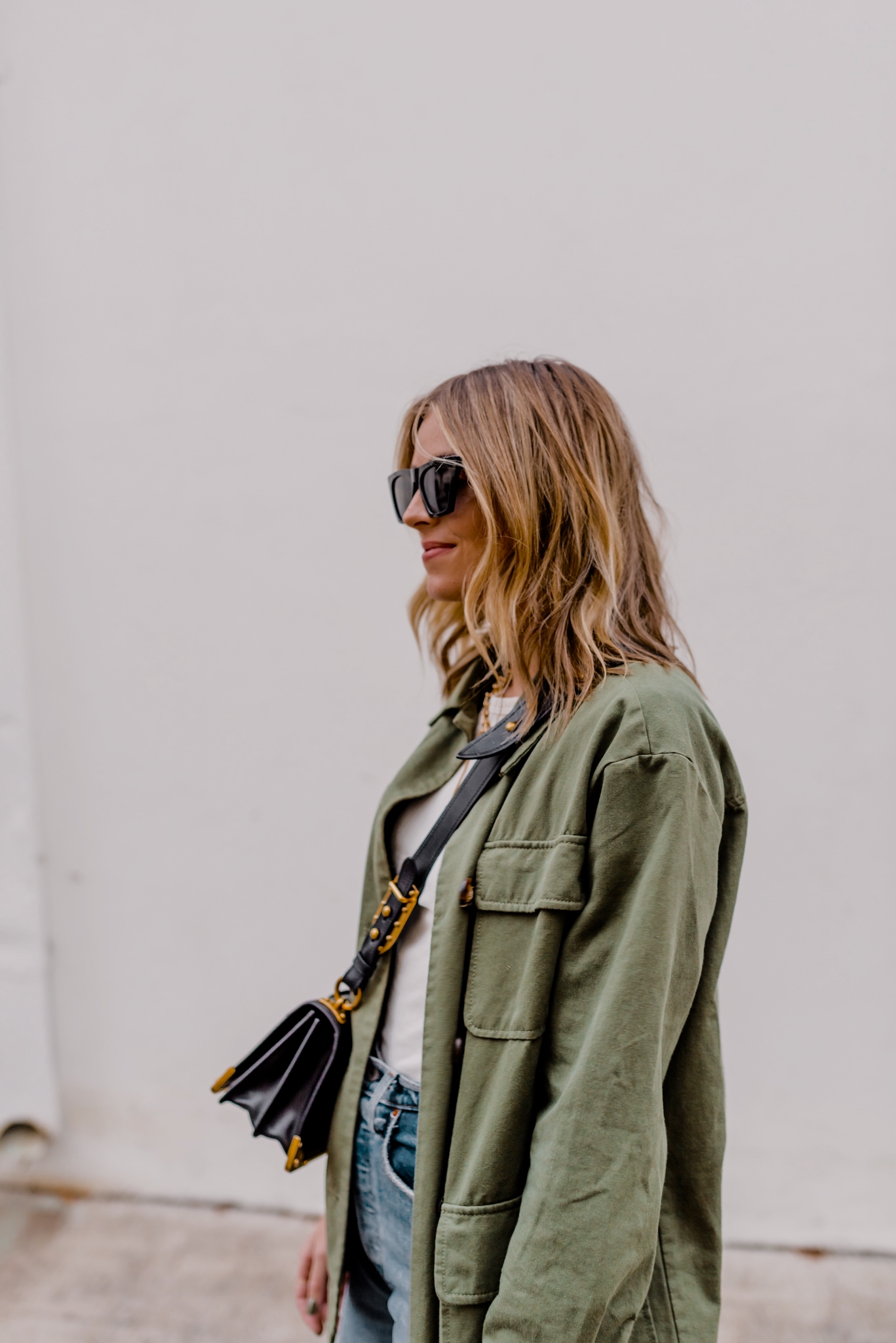 2 Ways To Style A Military Jacket - Camilla Thurman - Navy Grace |Military Jacket by popular San Diego fashion blog, Navy Grace: image of a woman wearing a military jacket, ribcage denim, white t-shirt, black combat boots, black frame sunglasses, and a Prada purse.
