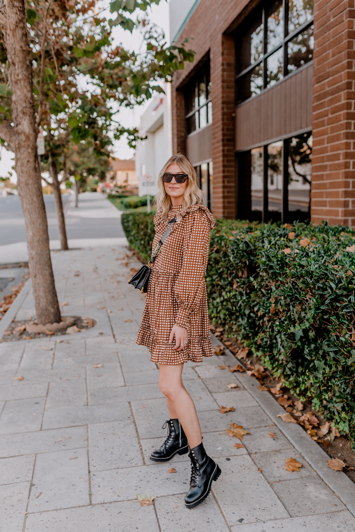 Top 10 Best Women's Combat Boots - Navy Grace - Camilla Thurman |Combat Boots by popular San Diego fashion blog, Navy Grace: image of a woman walking outside and wearing a Anthropologie Penny Gingham Mini Dress, Bloomingdales AQUA Women's Jax Combat Boots, Amazon Mosanana Square Cateye Sunglasses, and carrying a Prada Cashier bag.