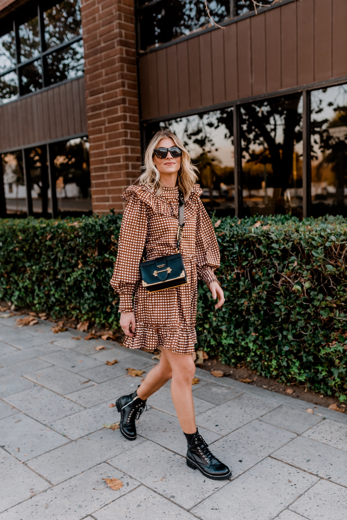 Top 10 Best Women's Combat Boots - Navy Grace - Camilla Thurman | Combat Boots by popular San Diego fashion blog, Navy Grace: image of a woman walking outside and wearing a Anthropologie Penny Gingham Mini Dress, Bloomingdales AQUA Women's Jax Combat Boots, Amazon Mosanana Square Cateye Sunglasses, and carrying a Prada Cashier bag.