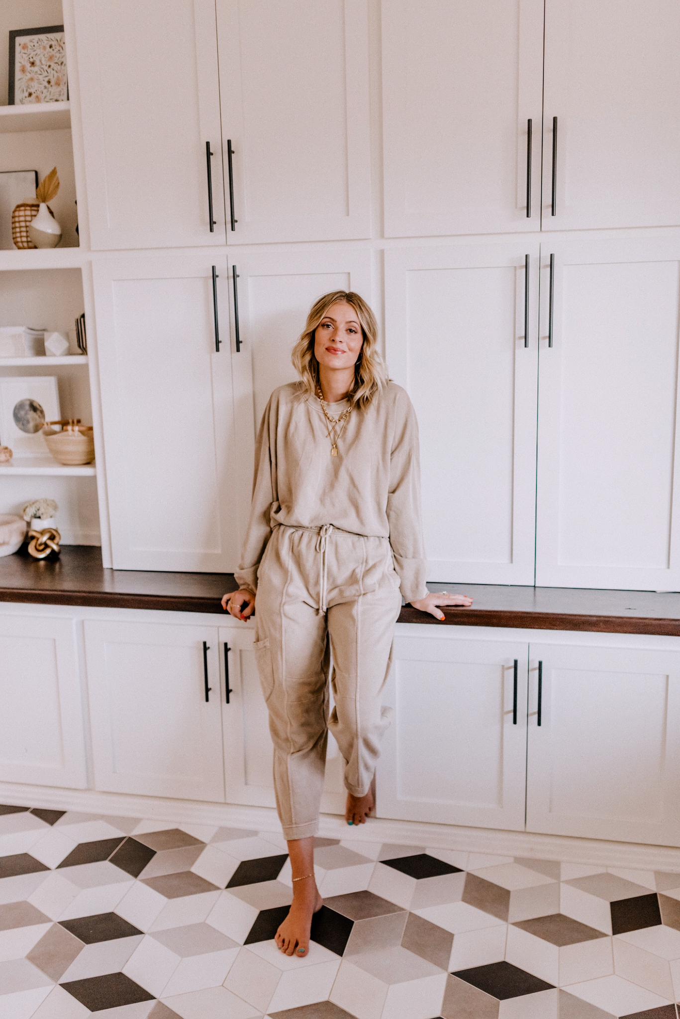 2020 Black Friday Deals by popular San Diego life and style blog, Navy Grace: image of a woman wearing a cream loungewear set and leaning back against some white cupboards.