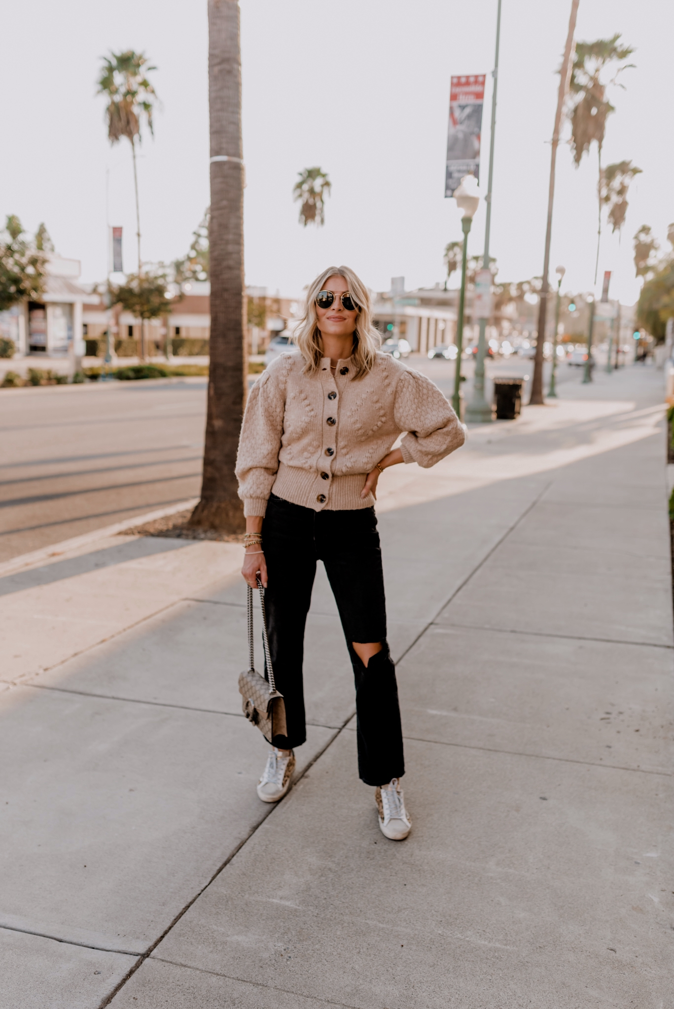 Best Cyber Monday Deals by popular San Diego life and style blog, Navy Grace: image of a woman wearing a cream button up bubble sleeve sweater, distressed black denim and Golden Goose sneakers.