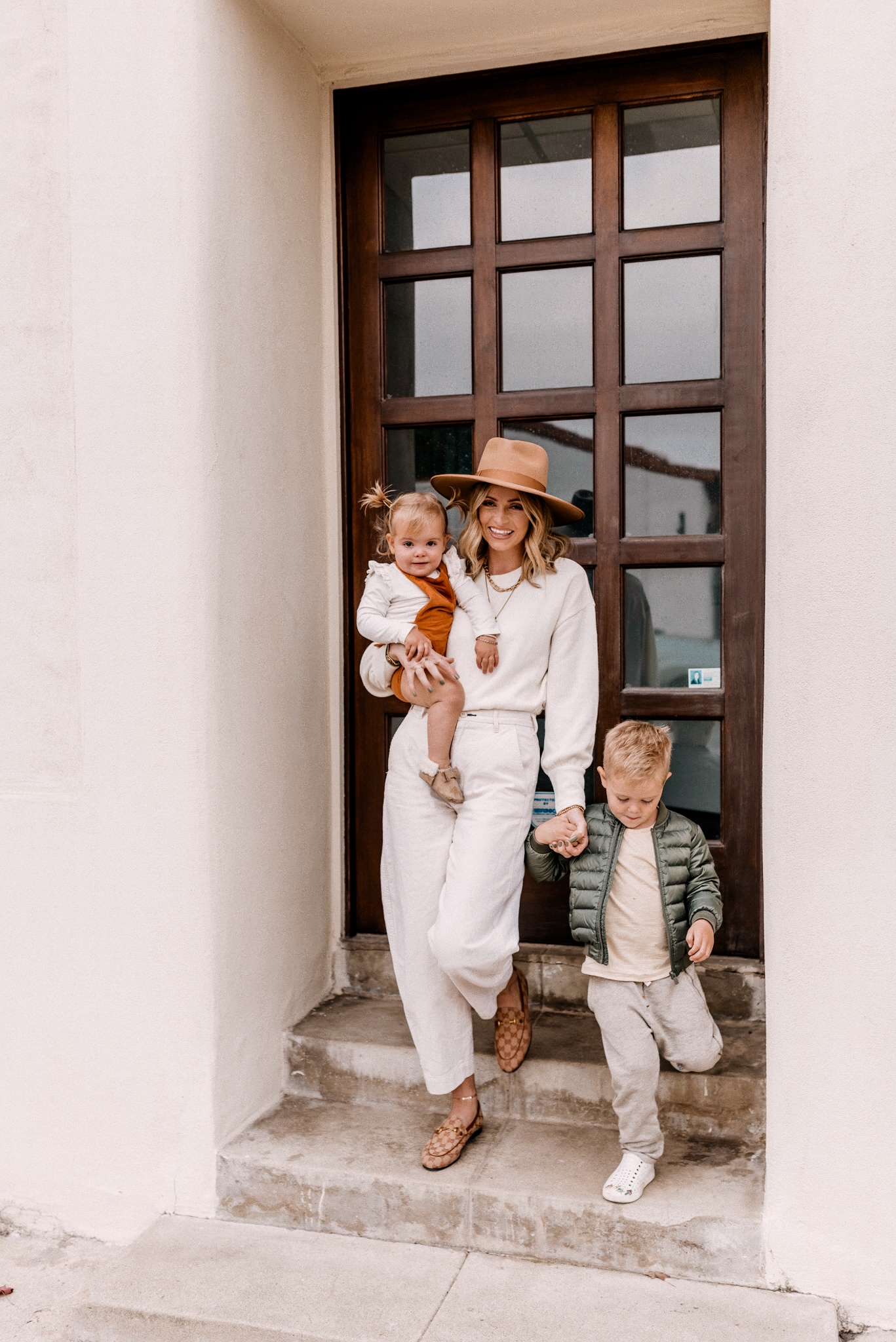 Fall fedora Hats |Kids Winter Clothes by popular San Diego motherhood blog, Navy Grace: image of a mom and her two young kids standing together on some cement steps.