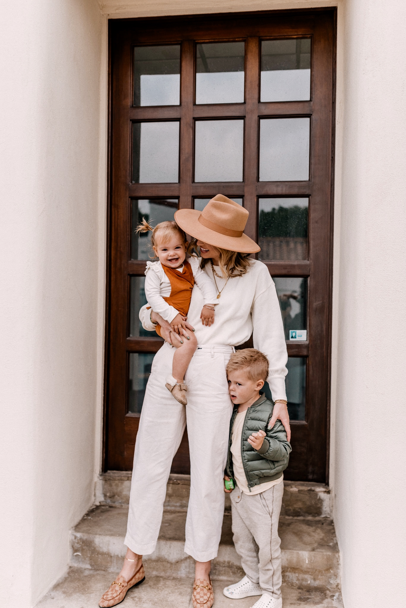 Affordable kids clothing |Kids Winter Clothes by popular San Diego motherhood blog, Navy Grace: image of a mom and her two young kids standing together on some cement steps.