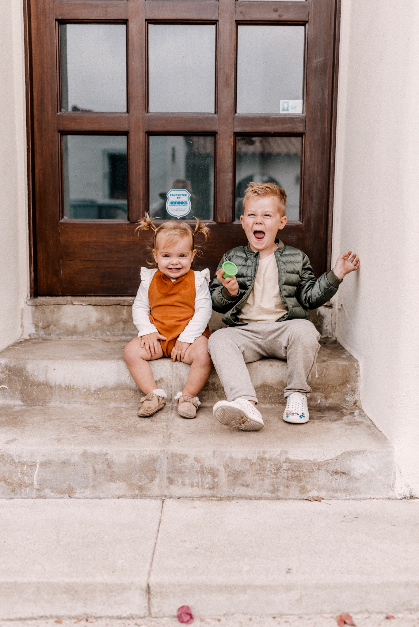 Affordable kids clothing |Kids Winter Clothes by popular San Diego motherhood blog, Navy Grace: image of young boy and girl sitting together on some cement steps.