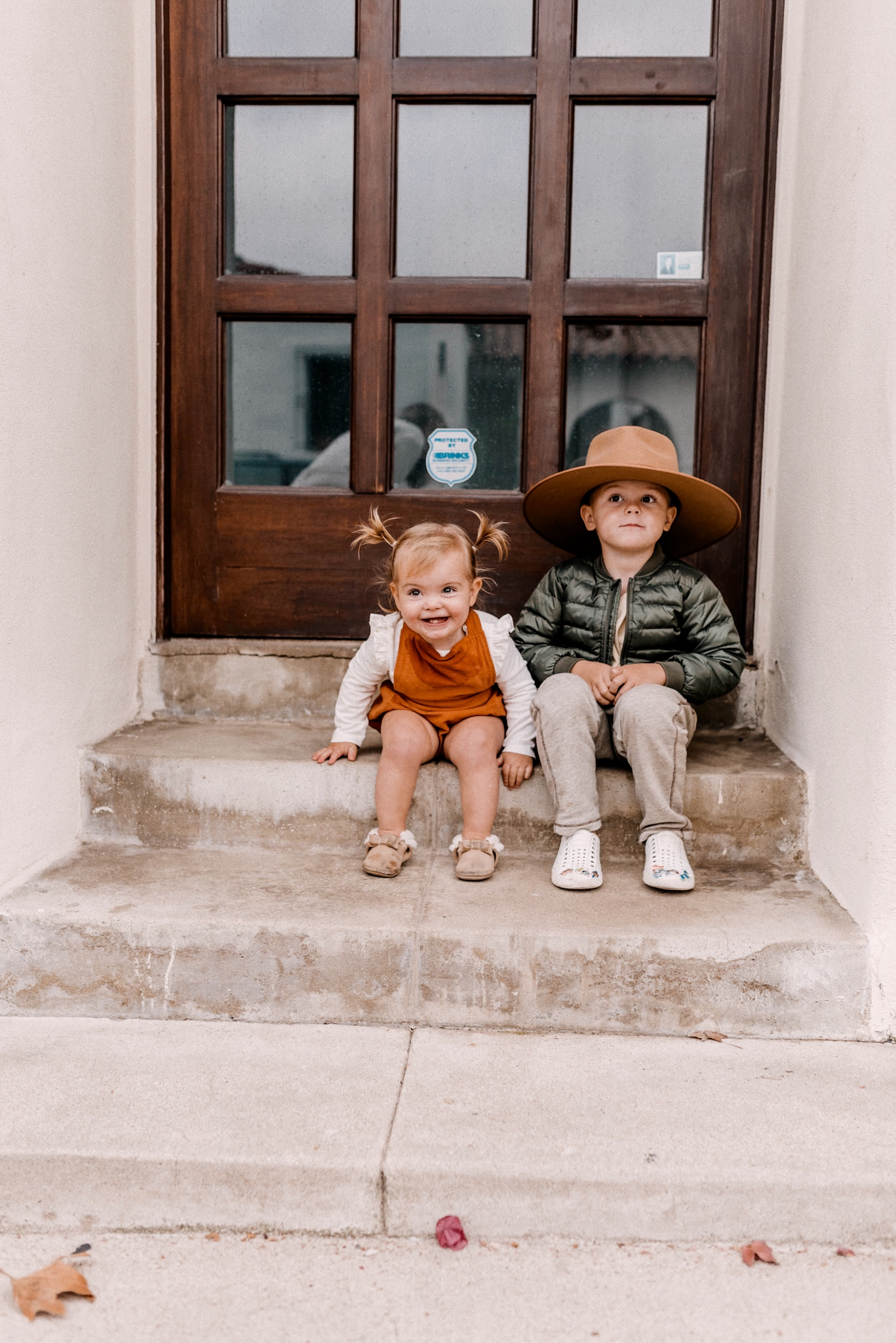 Fall fedora Hats | Kids Winter Clothes by popular San Diego motherhood blog, Navy Grace: image of a young boy and girl sitting together on some cement steps.