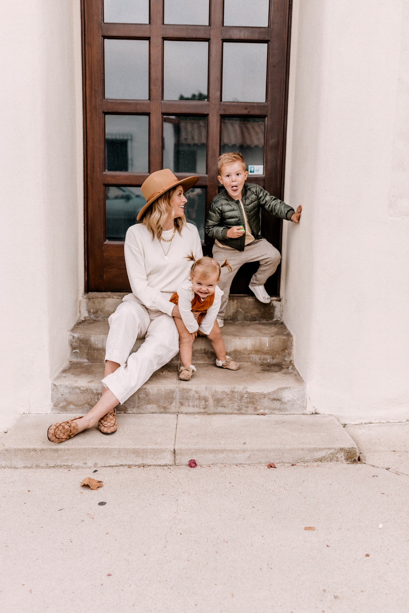 Fall fedora Hats | Kids Winter Clothes by popular San Diego motherhood blog, Navy Grace: image of a mom and her two young kids sitting together on some cement steps.