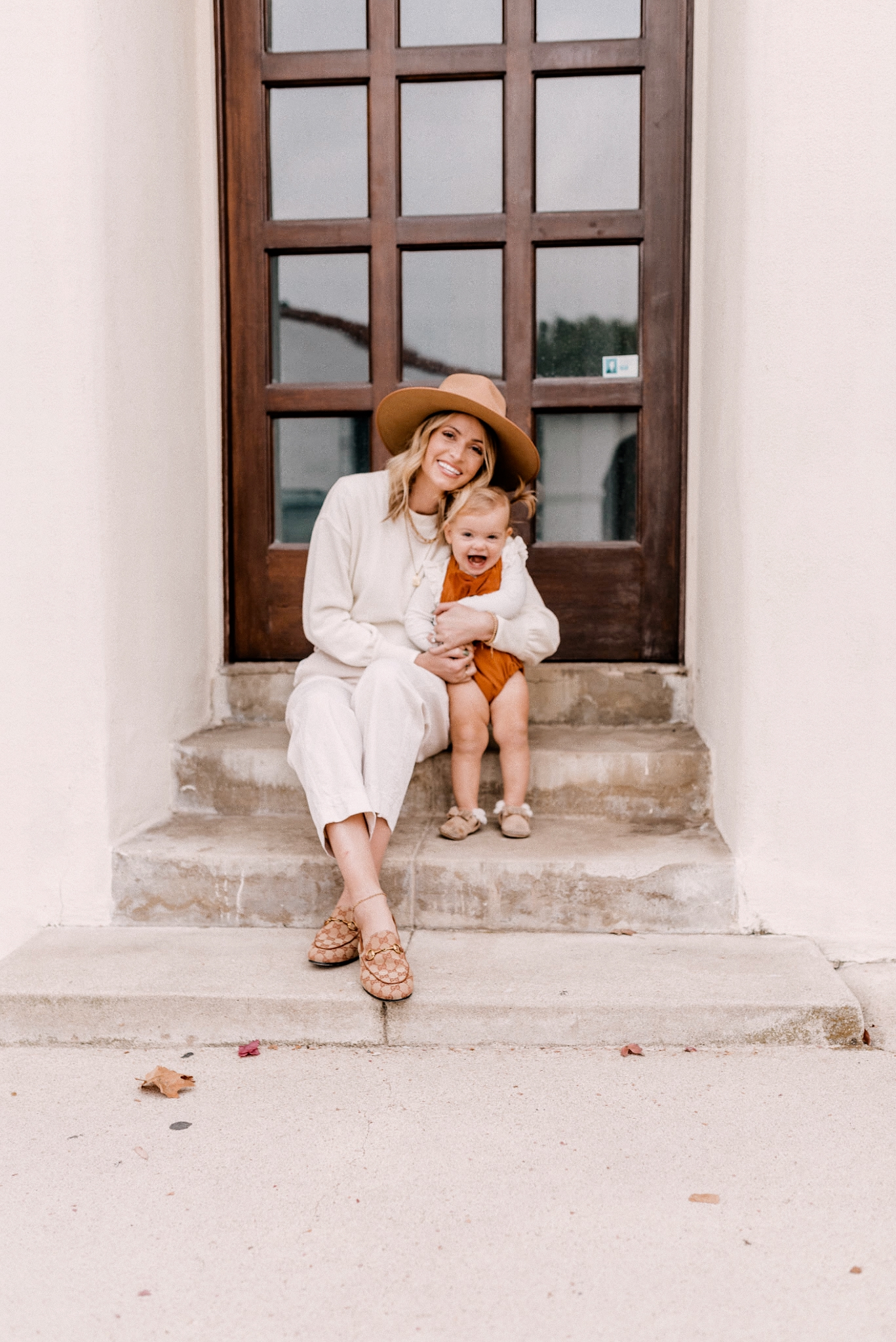 Fall fedora Hats |Fall fedora Hats | Fedora Hats by popular San Diego fashion blog, Navy Grace: image of a mom sitting on some steps with her baby daughter and wearing a Madewell Brushed Knit Puff-Sleeve Top, Everlane The Arc Canvas Pant,Gucci Women's Jordaan GG Canvas Loafers and Free People Rancher Felt Hat.