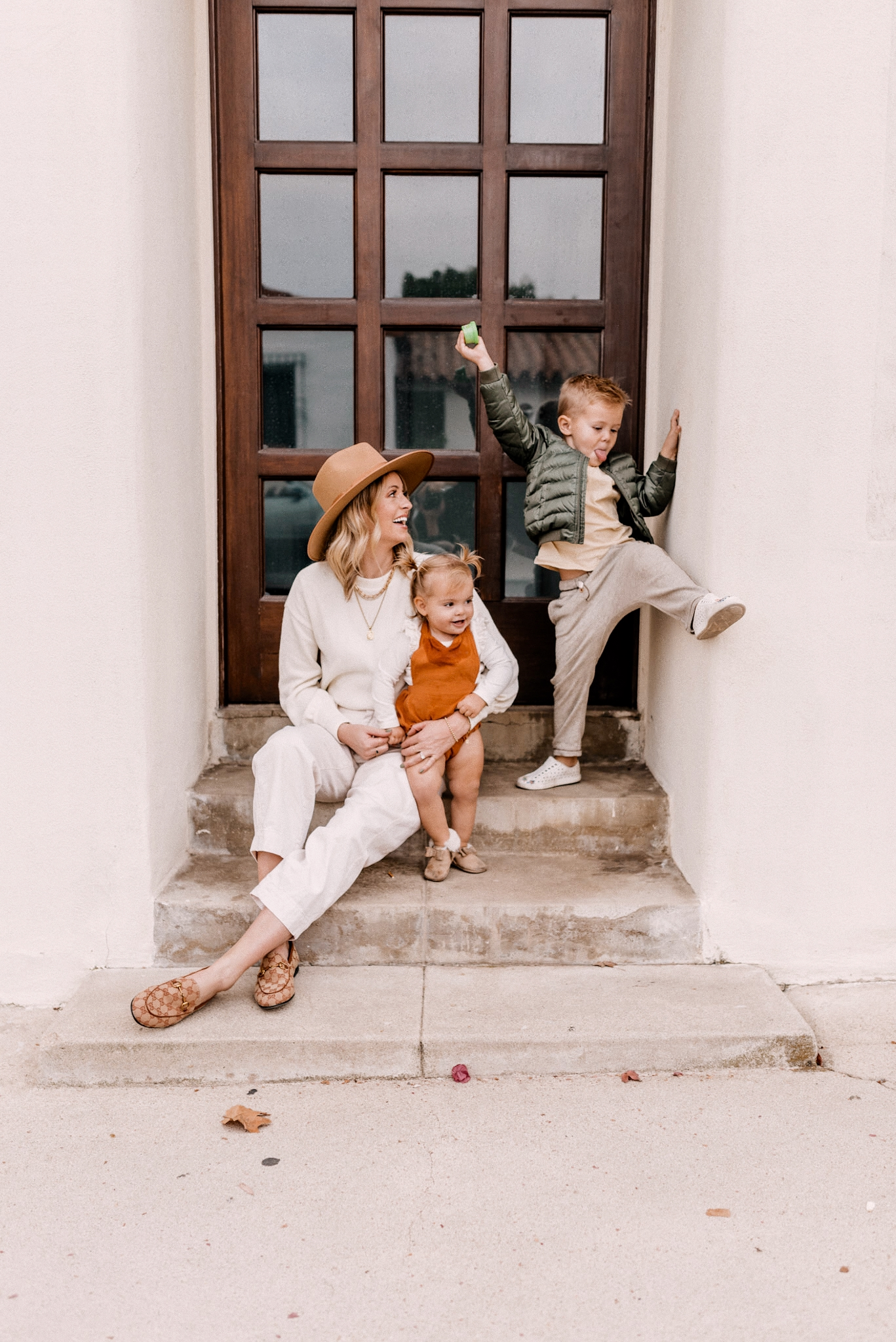 Affordable kids clothing |Kids Winter Clothes by popular San Diego motherhood blog, Navy Grace: image of a mom and her two young kids sitting together on some cement steps.