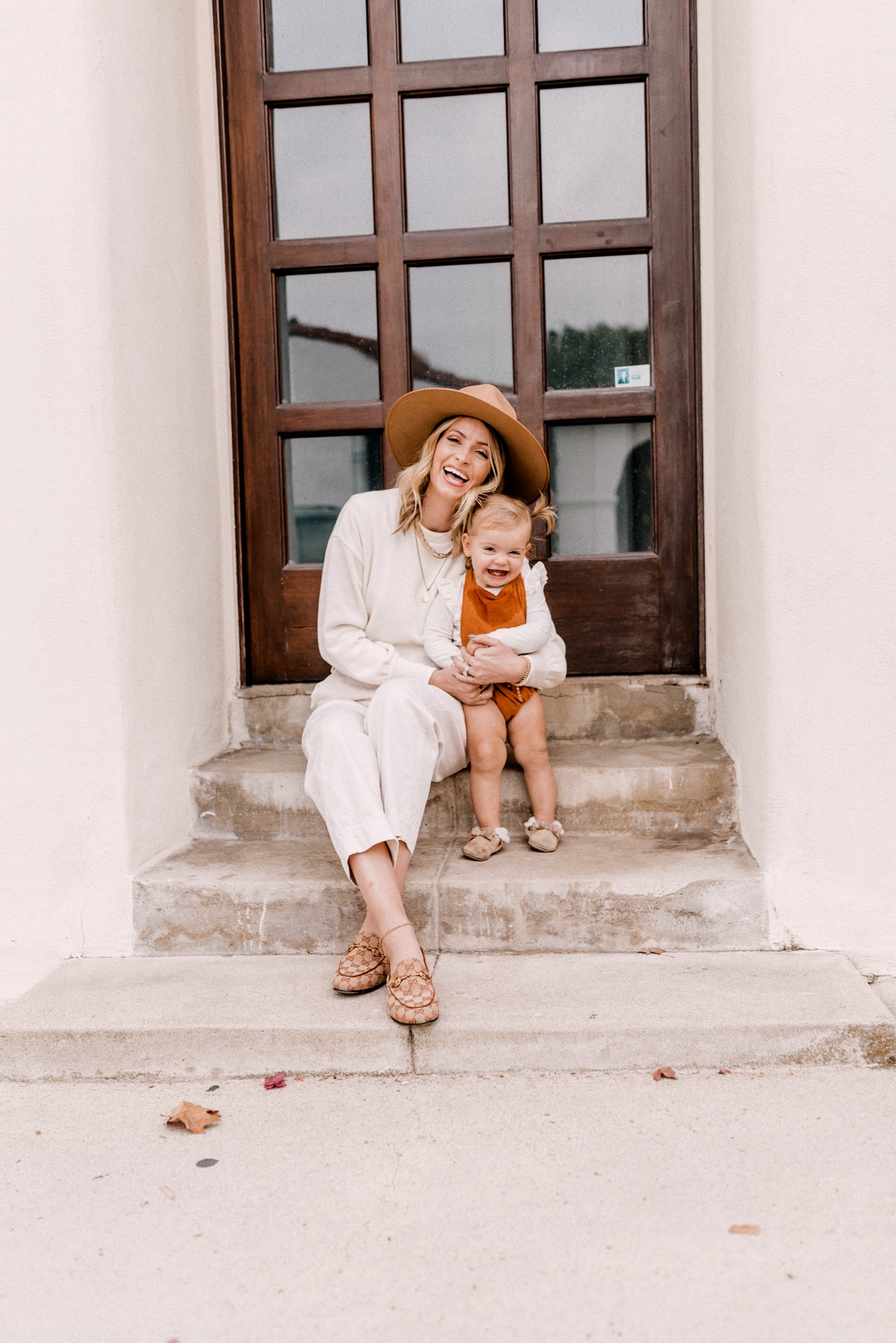 Fall fedora Hats |Kids Winter Clothes by popular San Diego motherhood blog, Navy Grace: image of a mom and her young daughter sitting together on some cement steps.