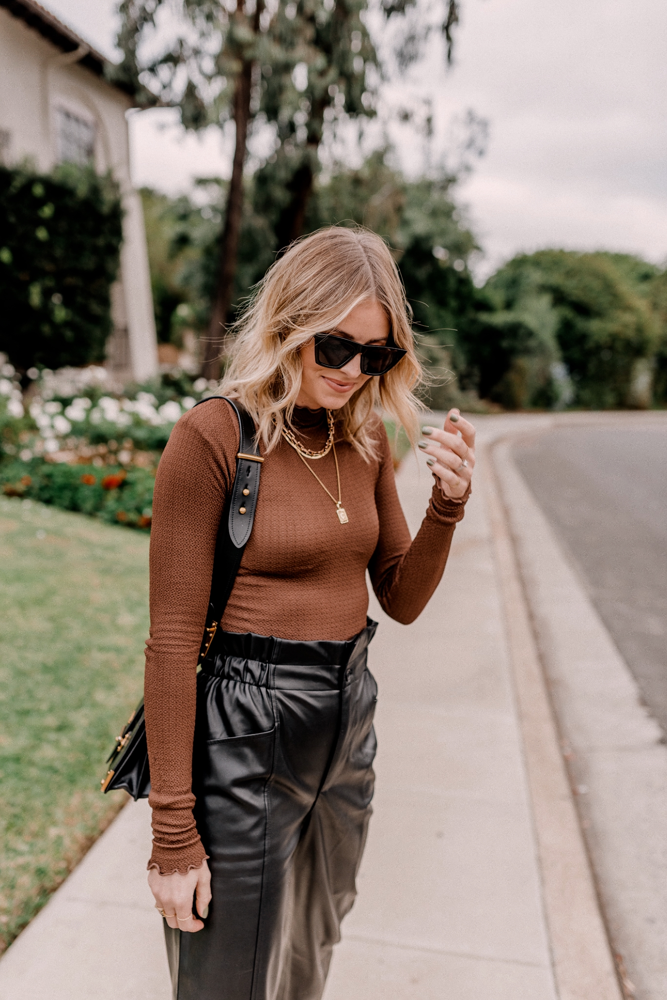 Mock Neck tops and Sweaters |Mock Neck Tops by popular San Diego fashion blog, Navy Grace: image of a woman wearing a long sleeve mock neck top, paper bag faux leather pants, black frame sunglasses, and black loafer slides.