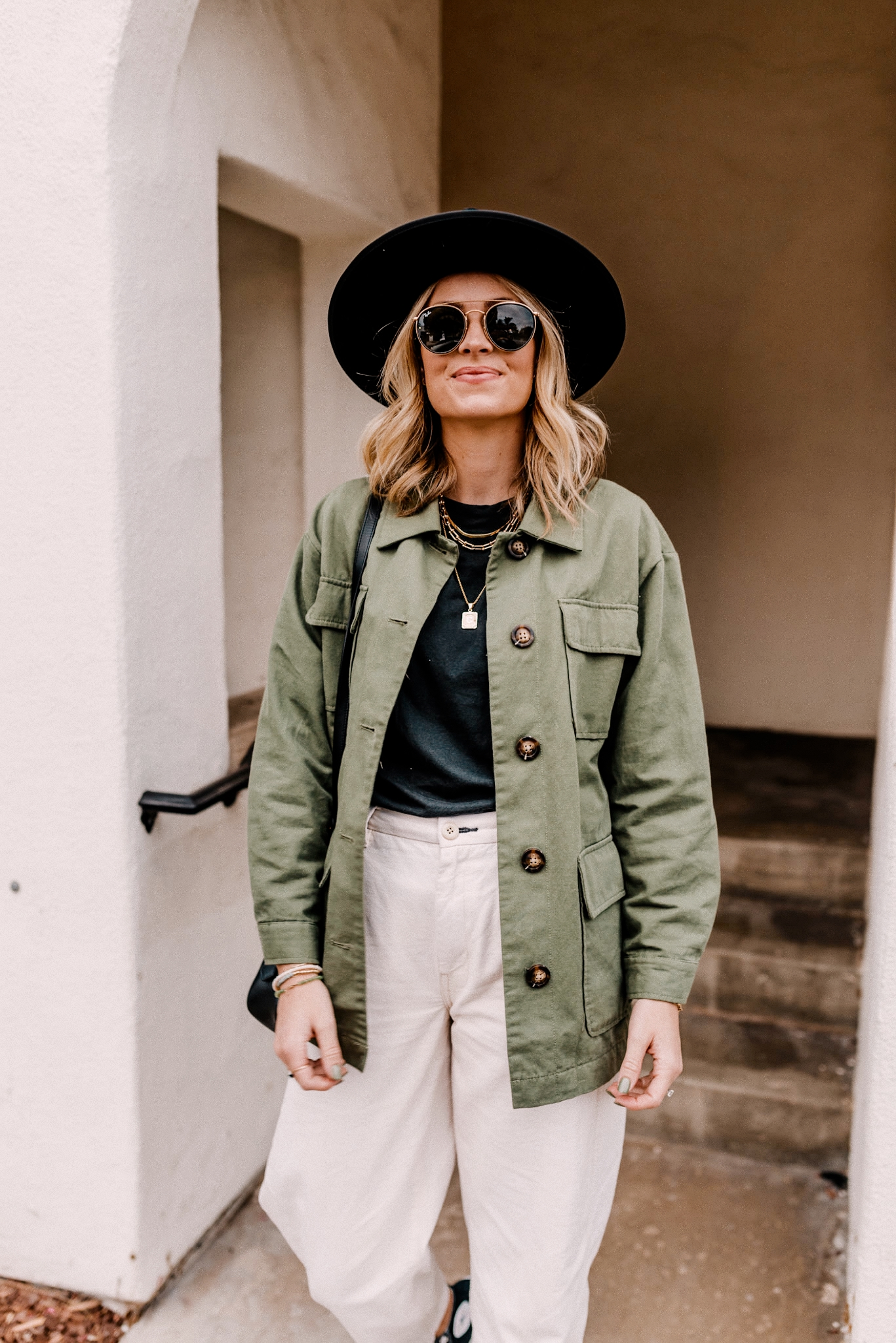 Military Jacket by popular San Diego fashion blog, Navy Grace: image of a woman wearing a military jacket, Ray-Ban sunglasses, canvas pants, black long sleeve t-shirt, black fedora hat, high top Converse sneakers, and Prada purse.