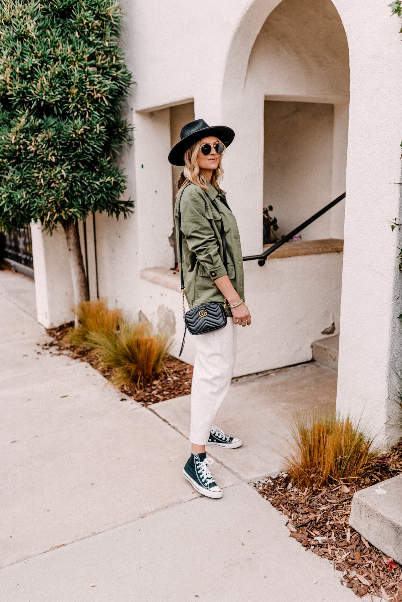 2 Ways To Style A Military Jacket - Camilla Thurman - Navy Grace |Military Jacket by popular San Diego fashion blog, Navy Grace: image of a woman wearing a military jacket, Ray-Ban sunglasses, canvas pants, black long sleeve t-shirt, black fedora hat, high top Converse sneakers, and Prada purse.