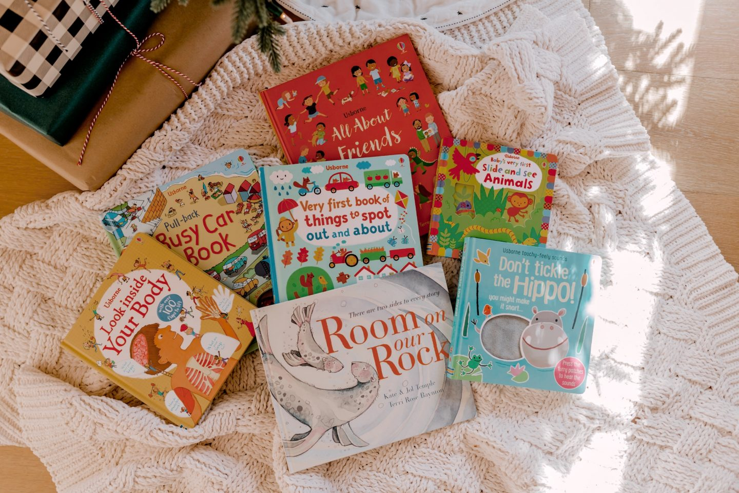 12 days of books for Christmas |12 Days of Books by popular San Diego lifestyle blog, Navy Grace: image of 12 children's books under a Christmas tree.