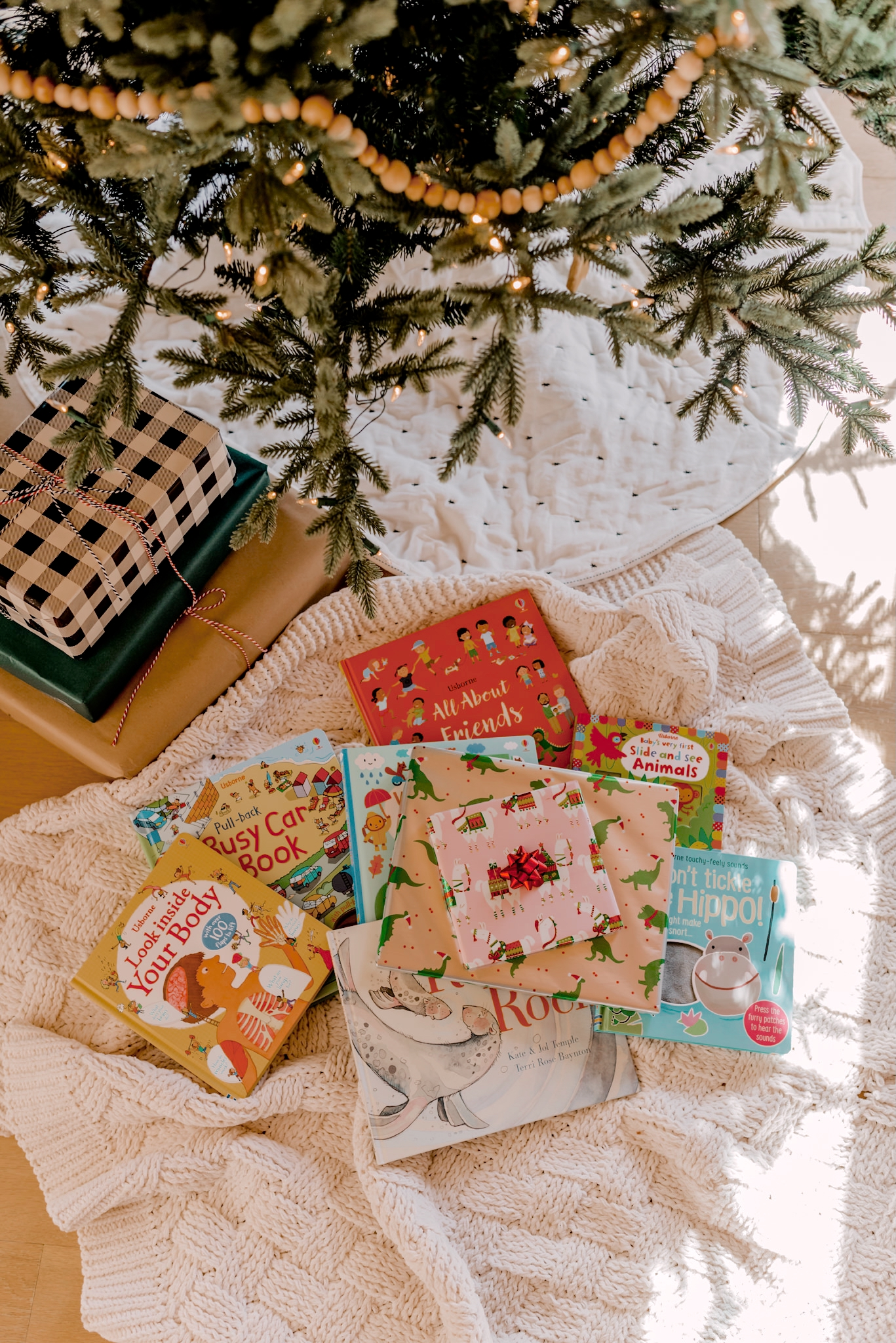 12 days of books for Christmas | 12 Days of Books by popular San Diego lifestyle blog, Navy Grace: image of 12 books under a Christmas tree.