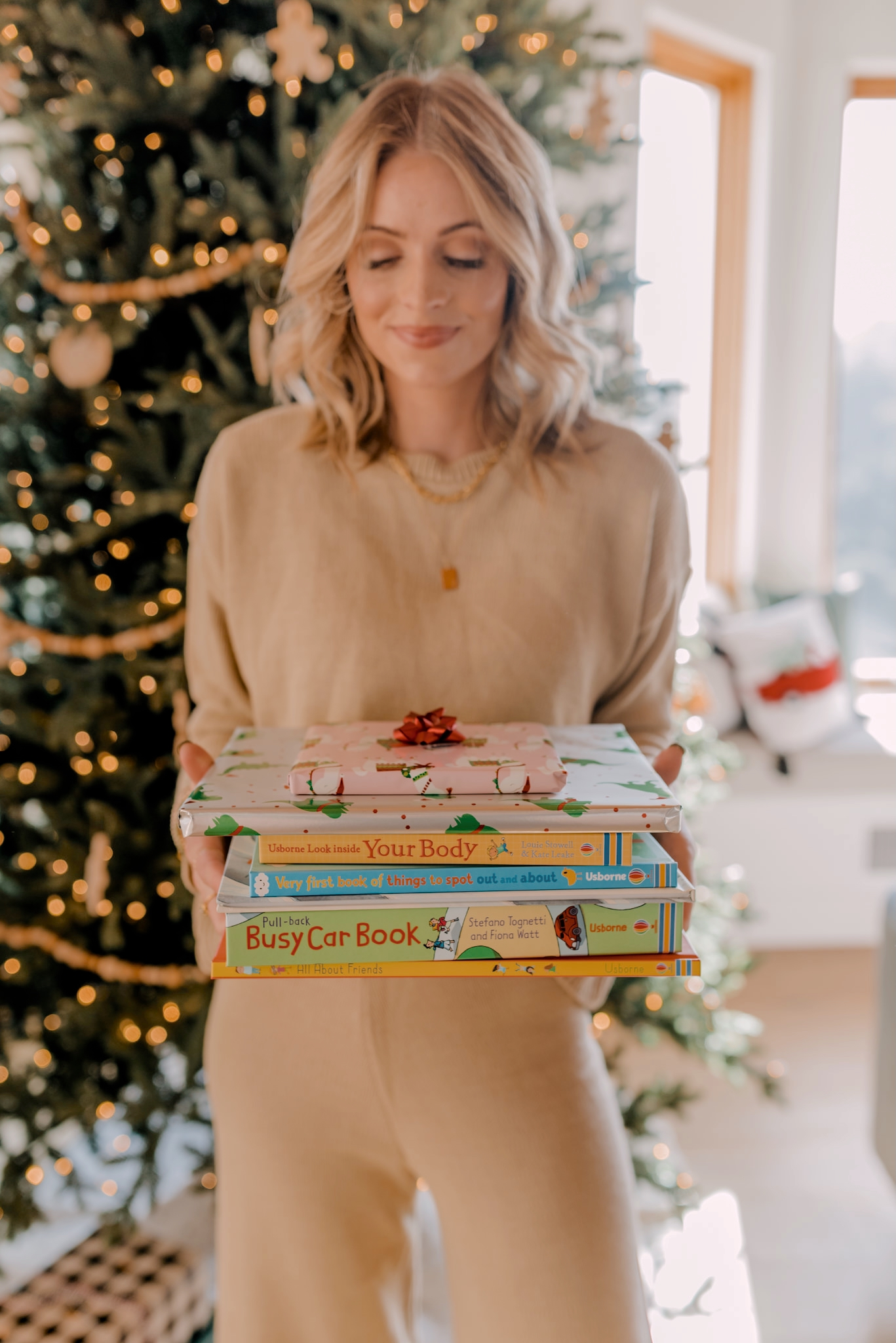 12 days of books for Christmas |12 Days of Books by popular San Diego lifestyle blog, Navy Grace: image of a woman standing in front of her Christmas tree and holding a pile of books.