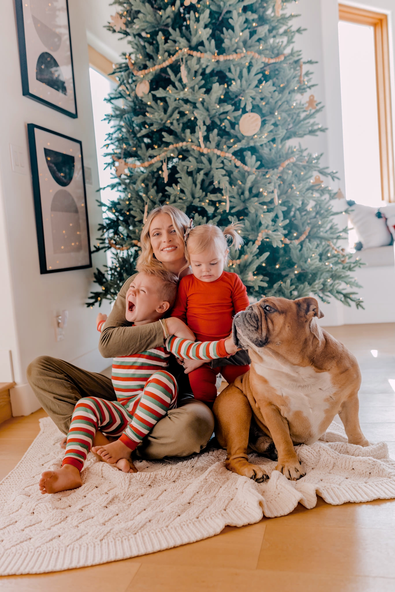 Stocking Stuffers for the Entire Family - Navy Grace - Camilla Thurman |Stocking Stuffers by popular San Diego life and style blog, Navy Grace: image of Camila Thurman and her two kids wearing Christmas pajamas and sitting on a knit blanket in front of their Christmas tree with their dog.