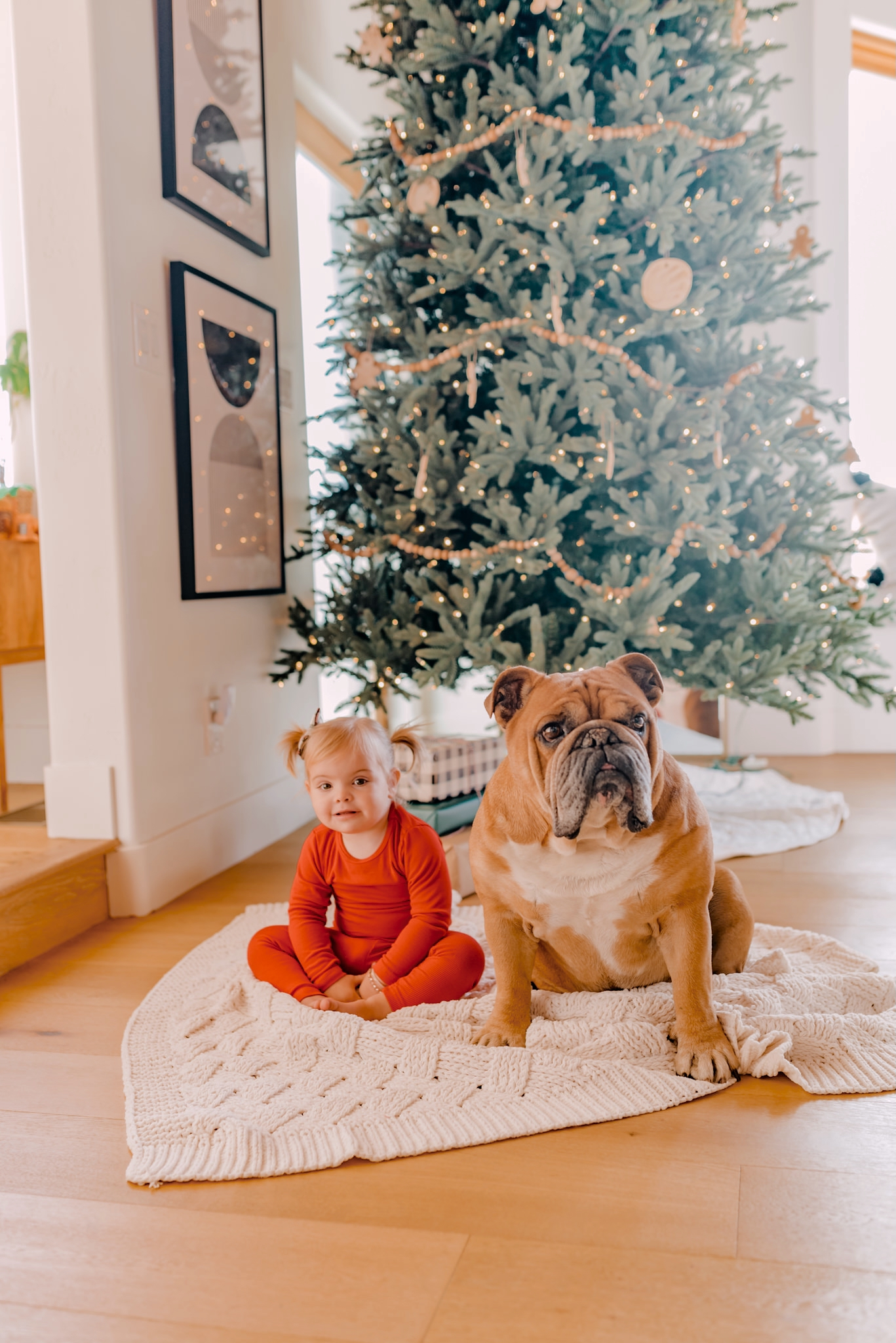 Stocking Stuffers for the Entire Family - Navy Grace - Camilla Thurman |Stocking Stuffers by popular San Diego life and style blog, Navy Grace: image of a little girl wearing red pajamas and sitting on a knit blanket in front of a Christmas tree with her dog.