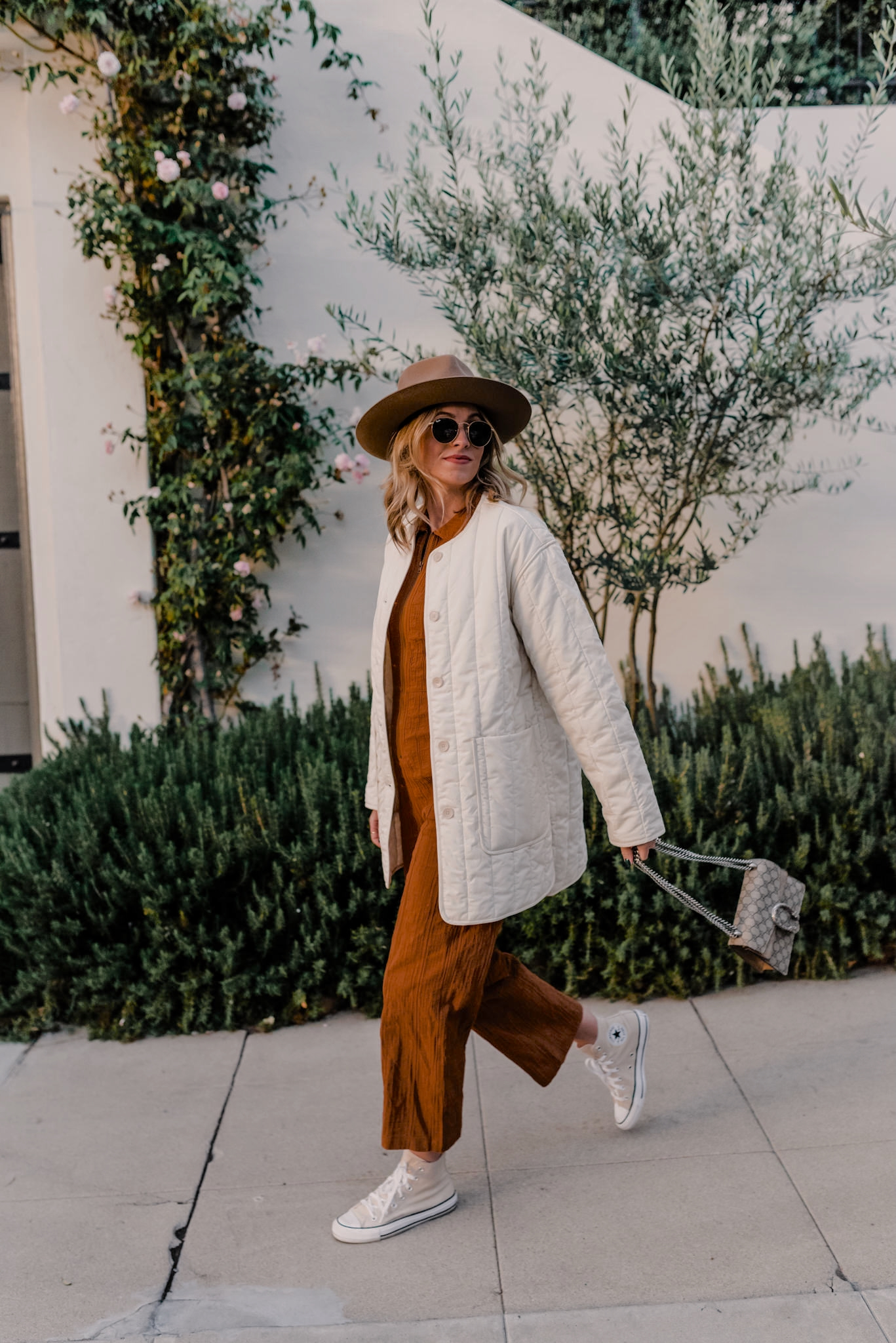 New Arrivals by popular San Diego fashion blog, Navy Grace: image of a woman wearing a White Quilted Jacket, Jumpsuit, Converse Sneakers, Fedora Hat, and Handbag.