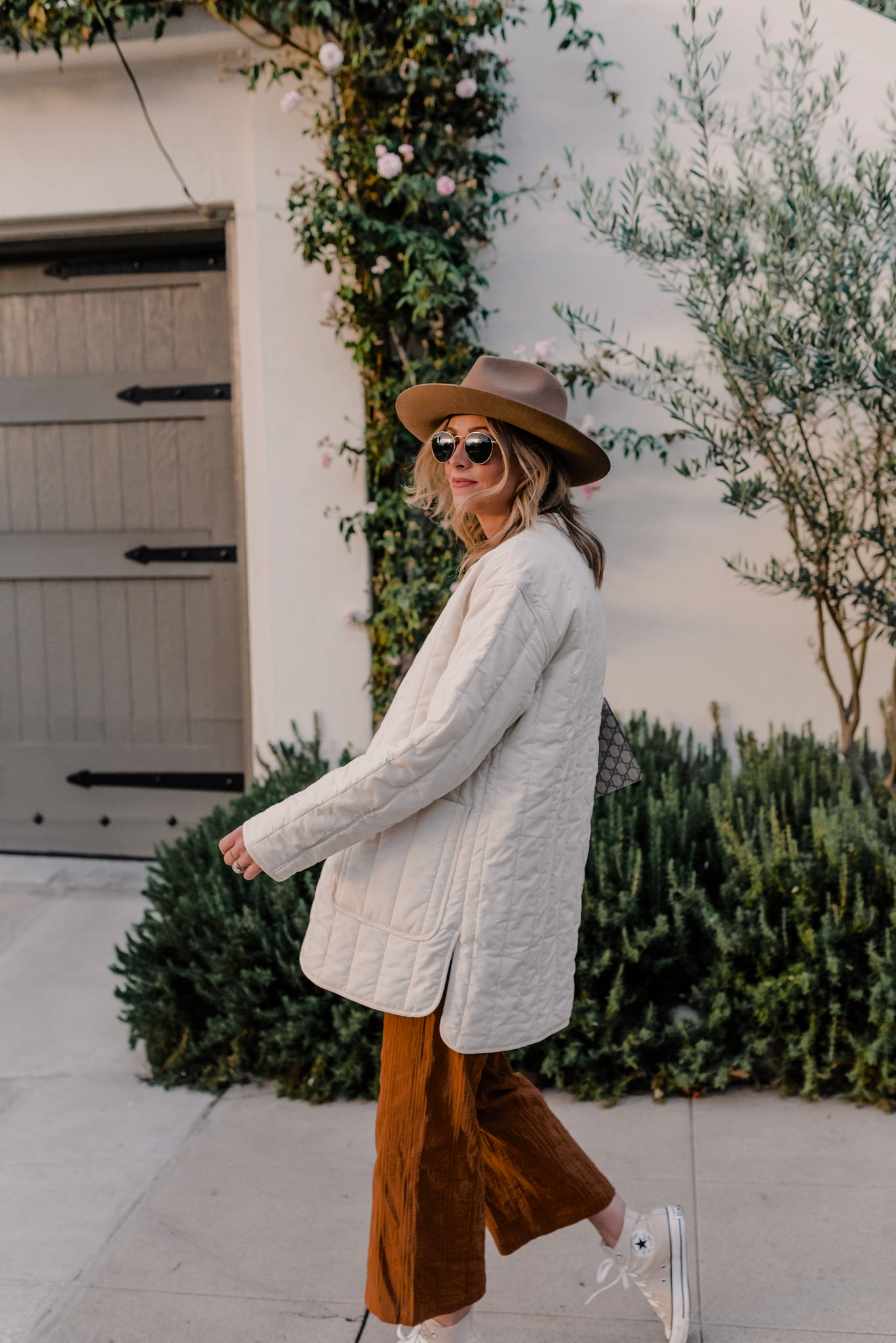 winter new arrivals im loving | New Arrivals by popular San Diego fashion blog, Navy Grace: image of a woman wearing a White Quilted Jacket, Jumpsuit, Converse Sneakers, Fedora Hat, and Handbag.