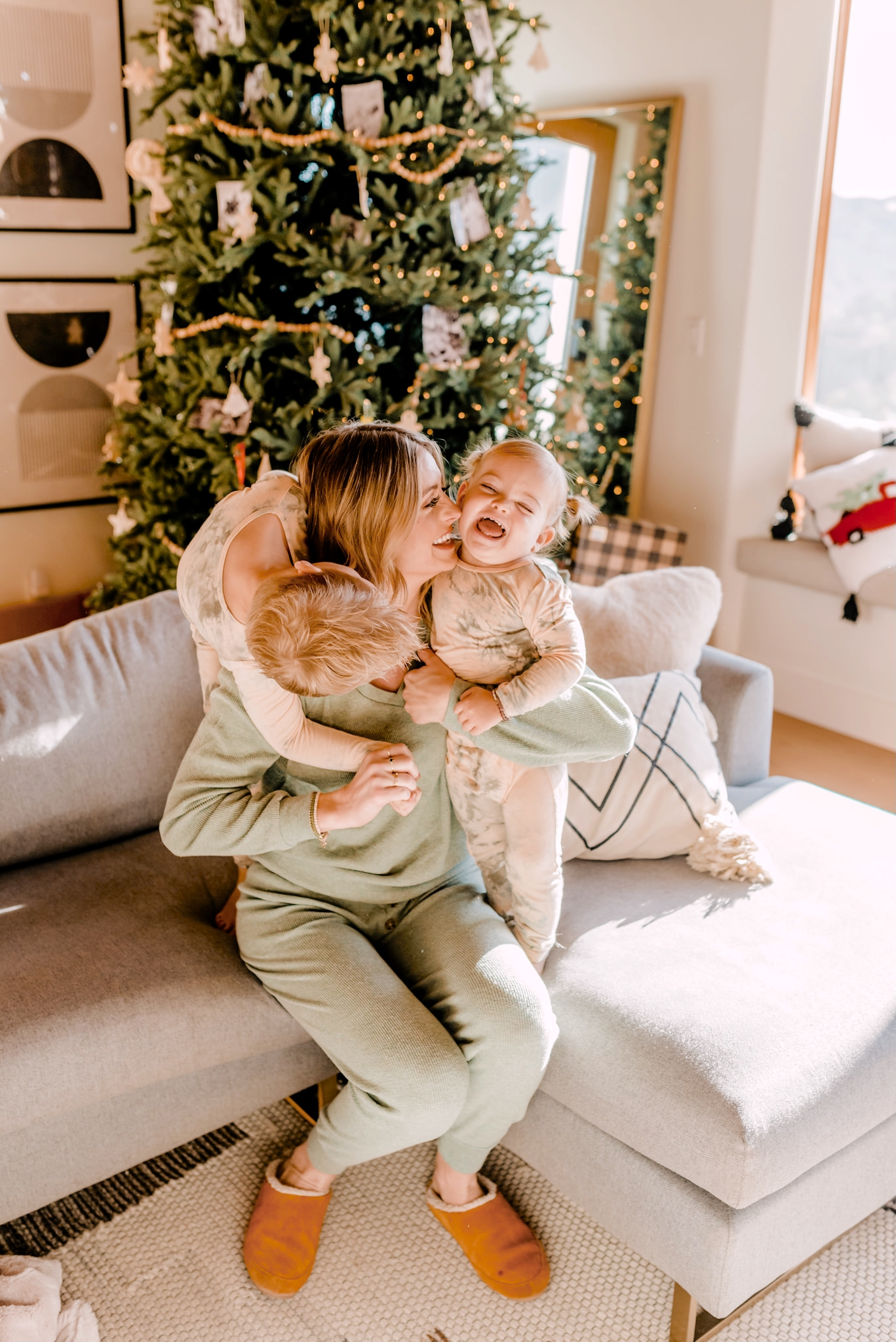 walmart+ |Walmart Membership by popular San Diego lifestyle blog, Navy Grace: image of a woman and her two small children wearing pajamas and sitting together on their grey sectional couch in front of their Christmas tree.