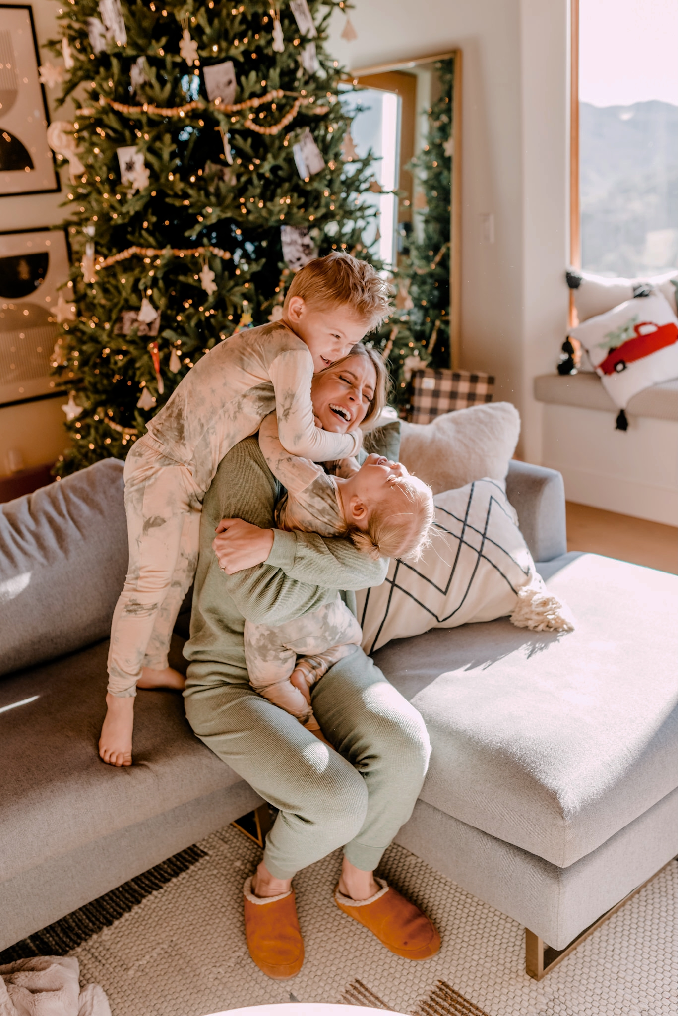 Walmart Membership by popular San Diego lifestyle blog, Navy Grace: image of a woman and her two small children wearing pajamas and sitting together on their grey sectional couch in front of their Christmas tree.