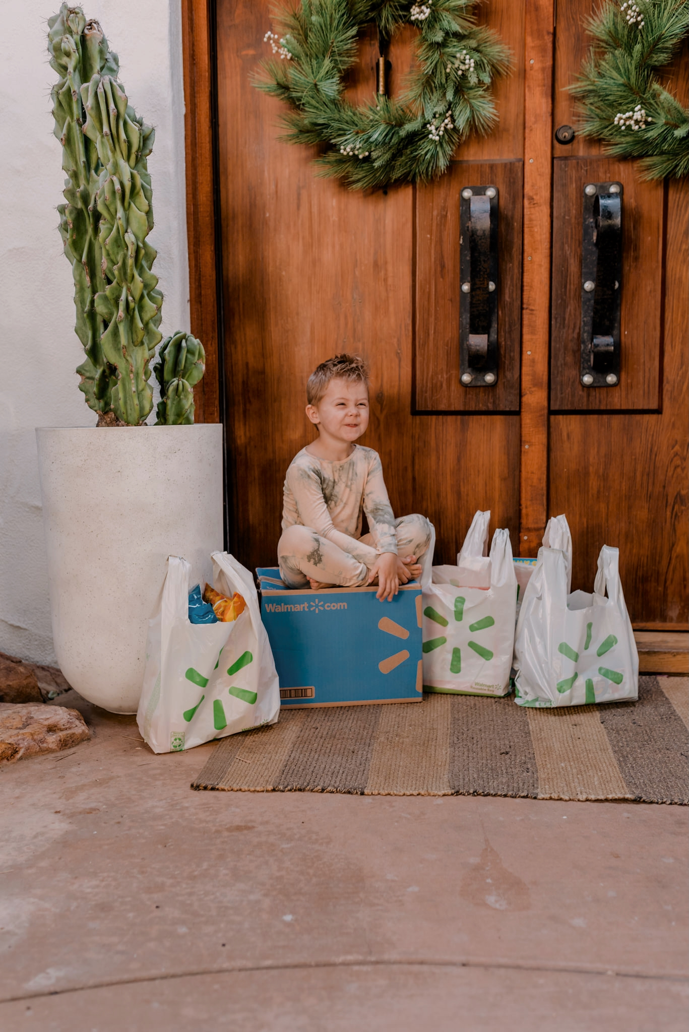 walmart+ |Walmart Membership by popular San Diego lifestyle blog, Navy Grace: image of a young boy sitting outside on top of a Walmart delivery box that's next to some Walmart shopping bags.