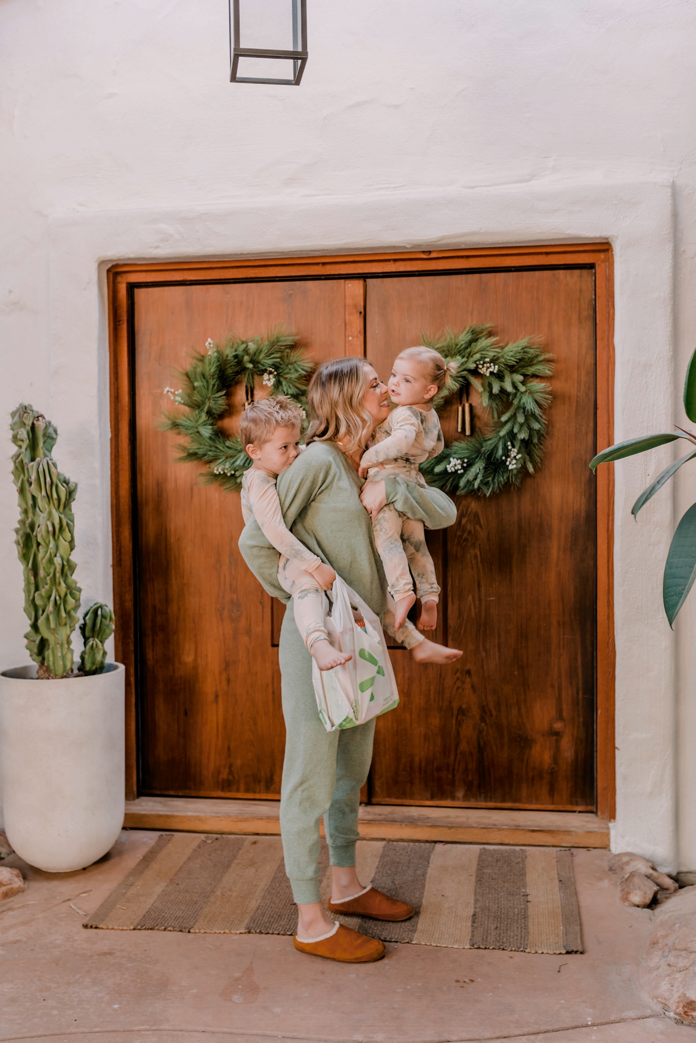 walmart+ | Walmart Membership by popular San Diego lifestyle blog, Navy Grace: image of a woman holding her children outside her front door while also holding a Walmart shopping bag.