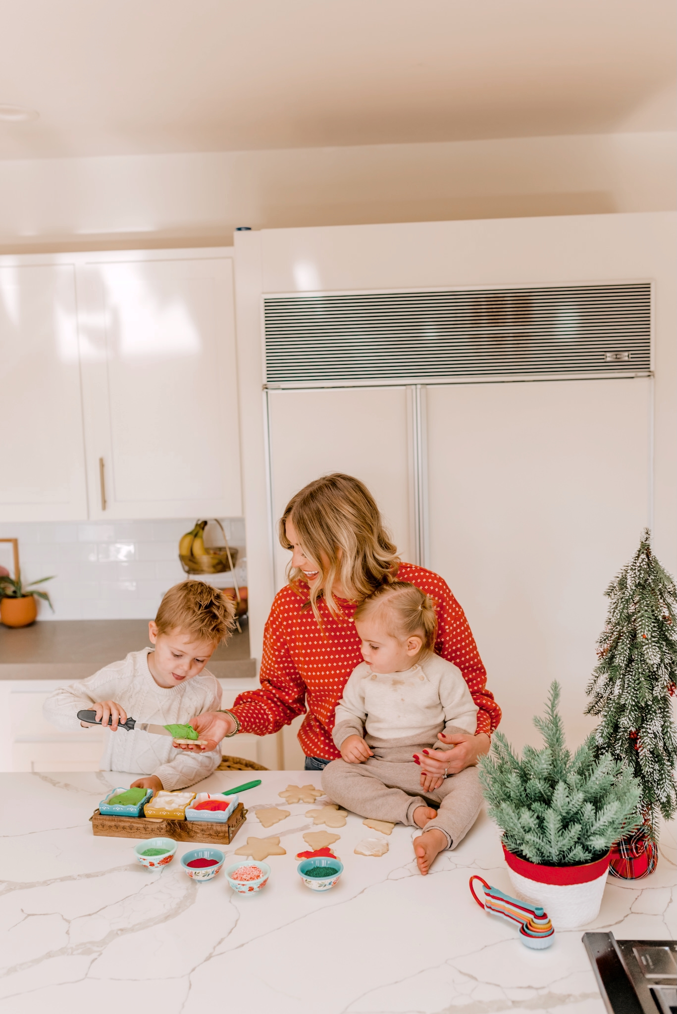 Holiday Traditions with Walmart by popular San Diego lifestyle blog, Navy Grace: image of a mom and her two small children decorating Christmas sugar cookies in their kitchen.