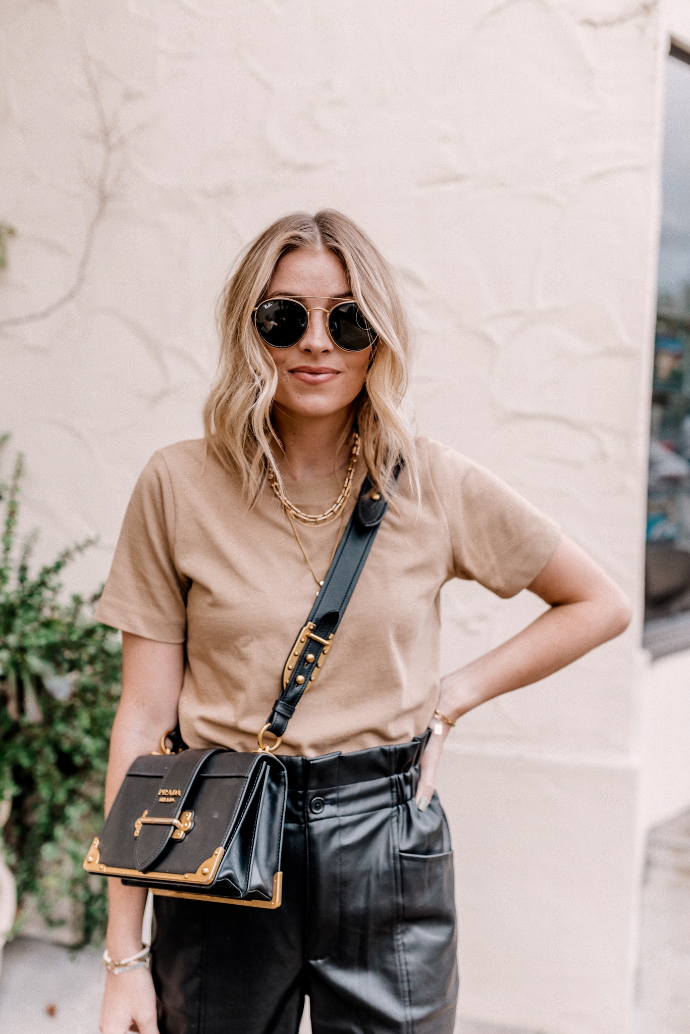 8 Faux Leather Pants | Faux Leather Pants by popular San Diego fashion blog, Navy Grace: image of a woman wearing a basic cotton tee, paper bag faux leather pants, ray-ban sunglasses, and Converse sneakers.