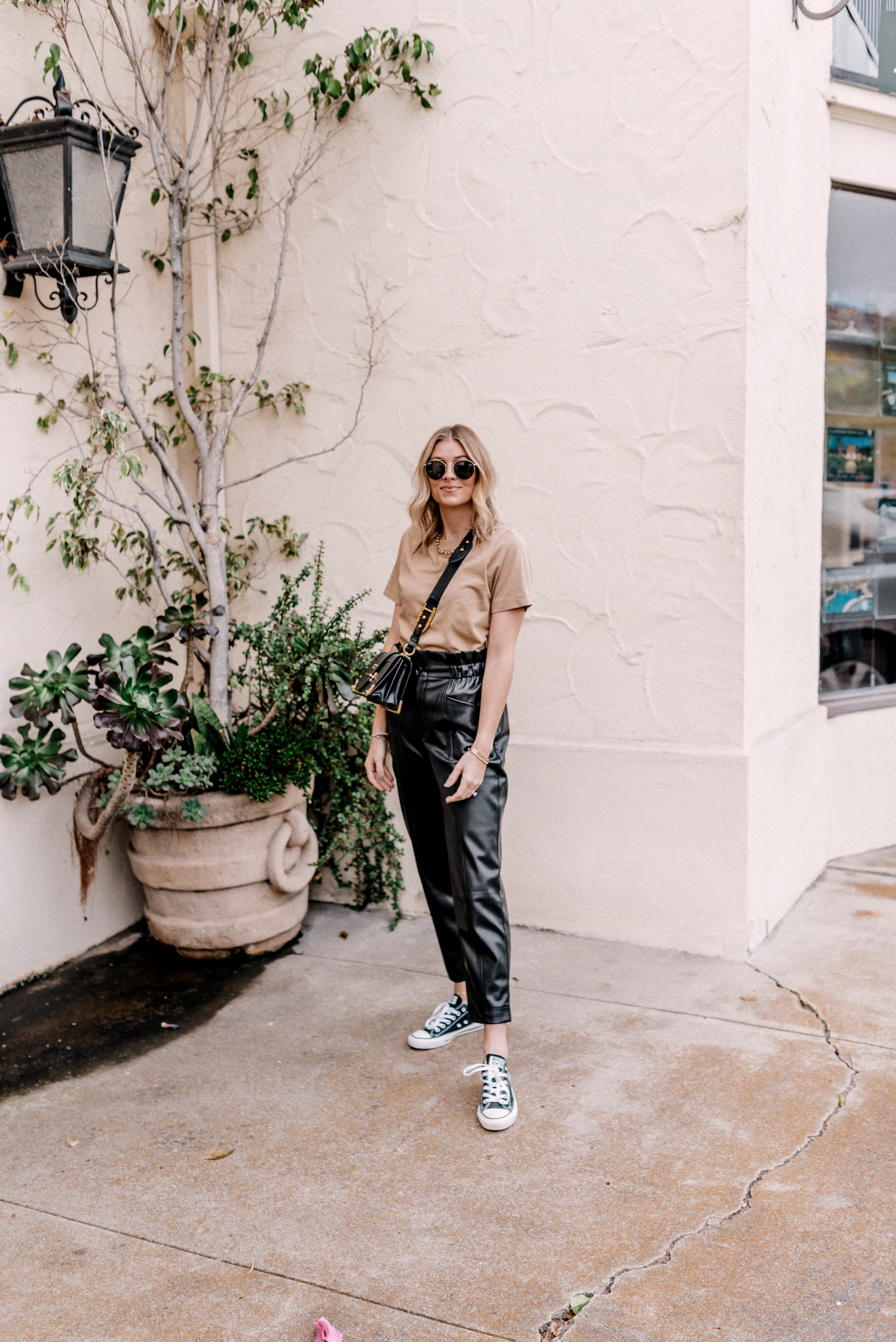 8 Faux Leather Pants  Faux Leather Pants by popular San Diego fashion blog, Navy Grace: image of a woman wearing a basic cotton tee, paper bag faux leather pants, ray-ban sunglasses, and Converse sneakers.