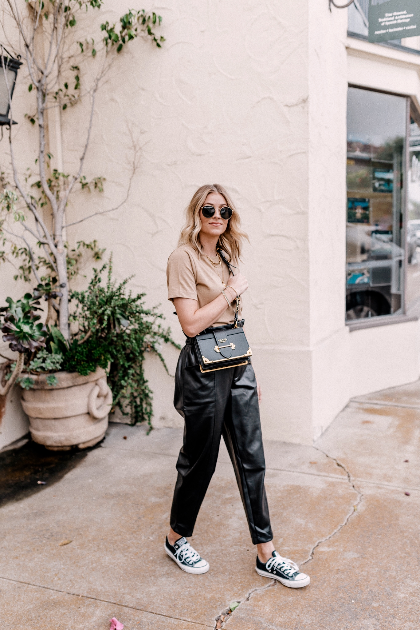 8 Faux Leather Pants |Faux Leather Pants by popular San Diego fashion blog, Navy Grace: image of a woman wearing a basic cotton tee, paper bag faux leather pants, ray-ban sunglasses, and Converse sneakers.
