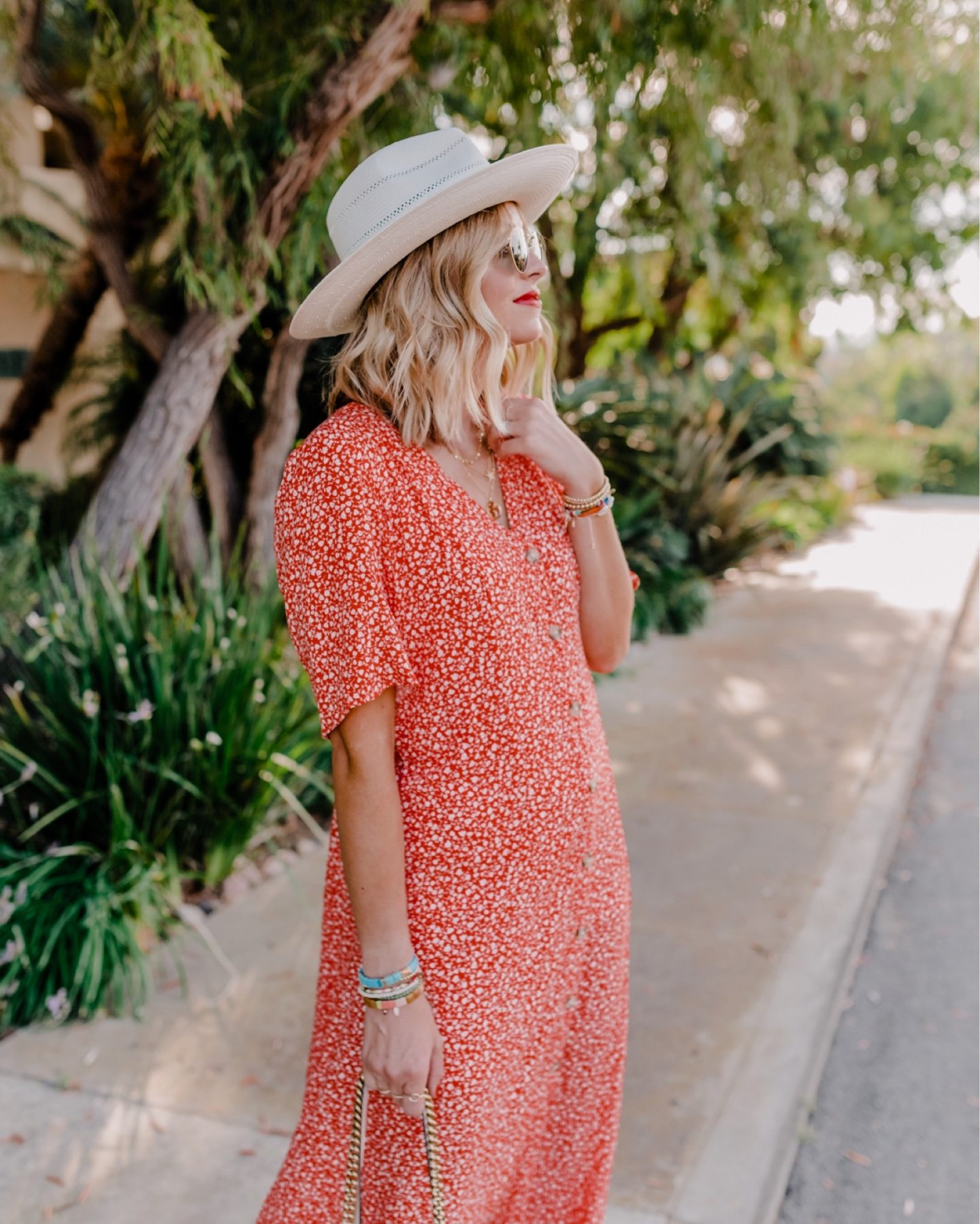 Top Looks of 2020 |Top Looks by San Diego fashion blog, Navy Grace: image of a woman wearing a red and white floral button front dress and white straw fedora hat.