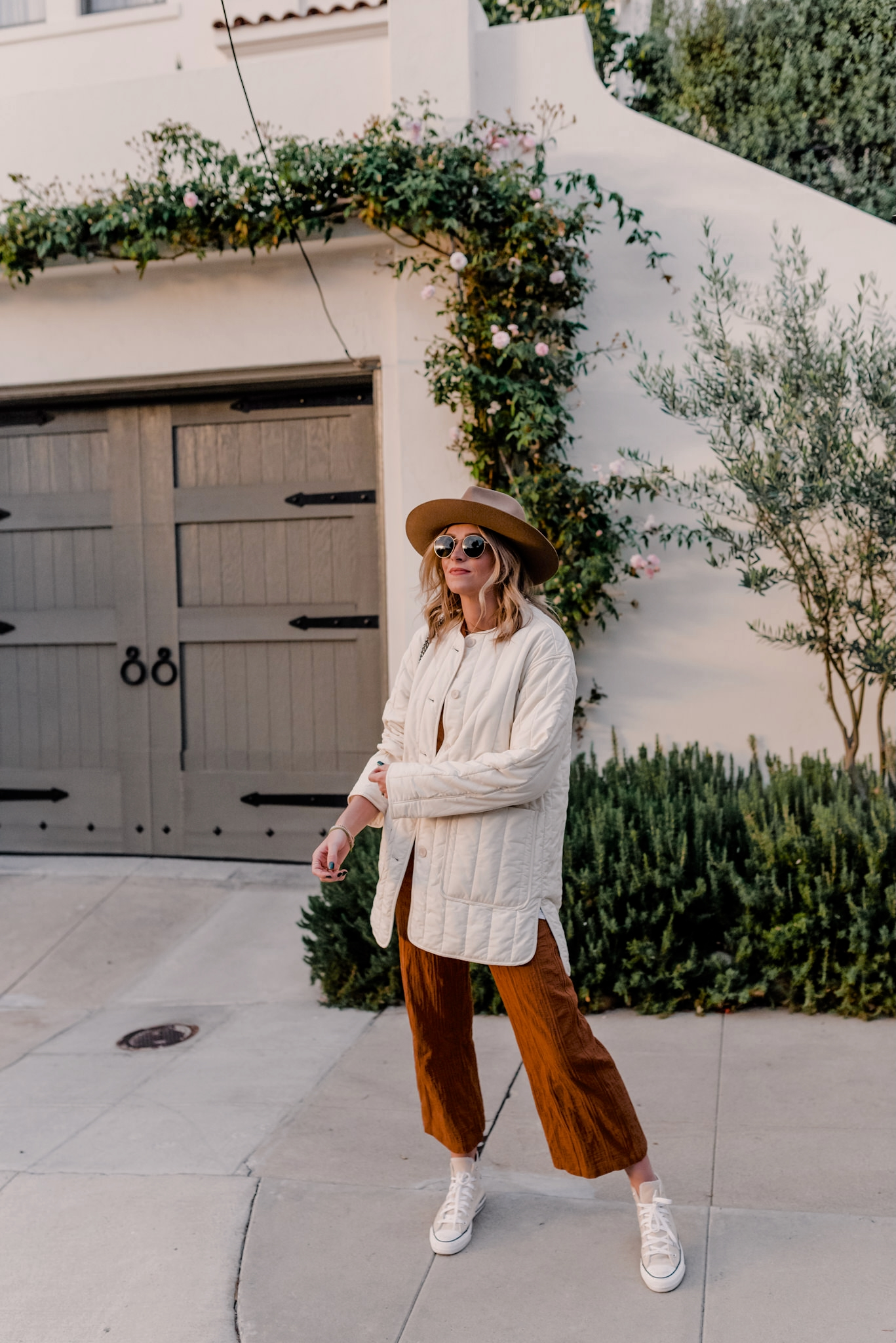 Top Looks of 2020 |Top Looks by San Diego fashion blog, Navy Grace: image of a woman wearing a tan quilted jacket, brown wide brim felt hat, tan Converse sneakers, and wide leg pants.