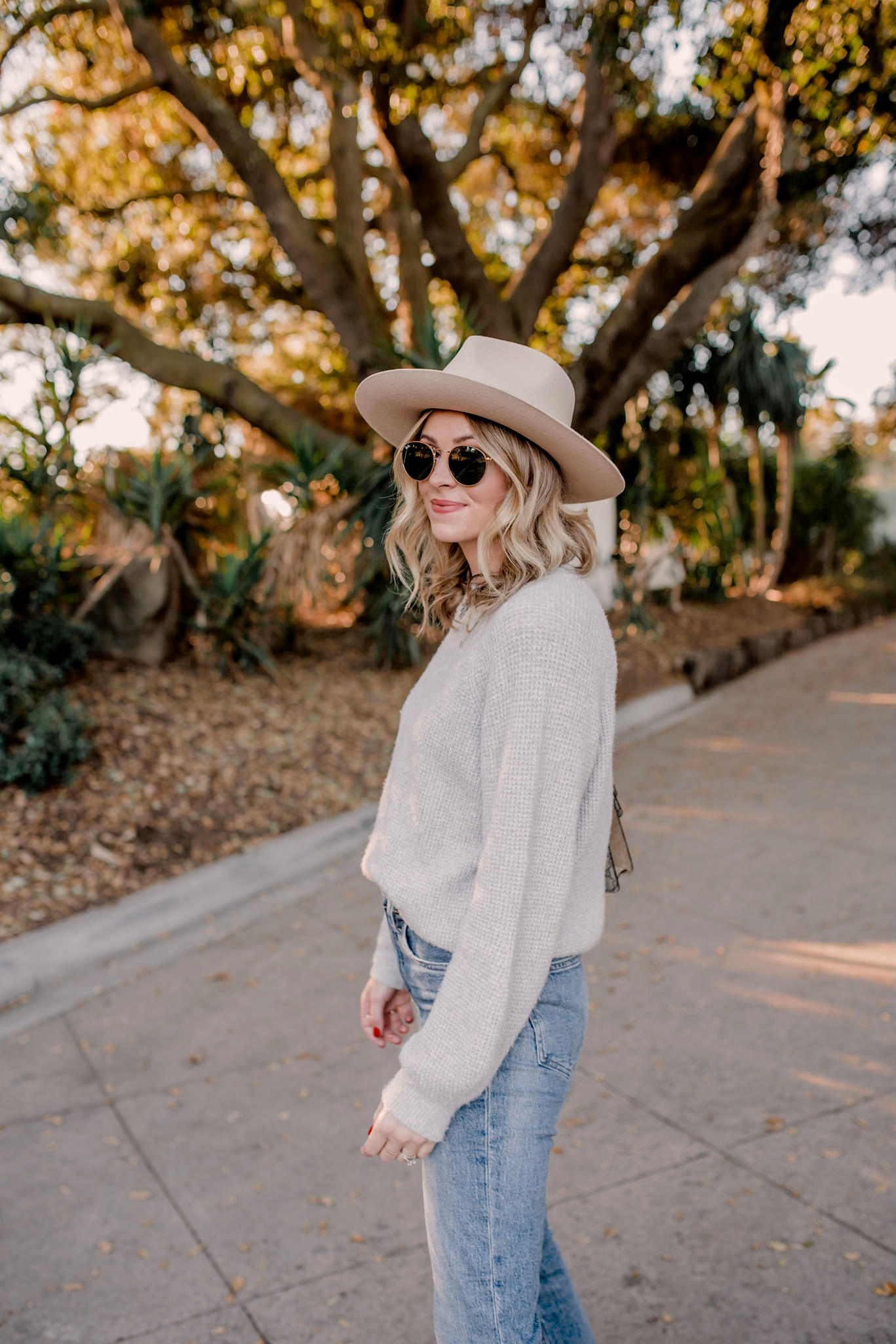 top 10 items of 2020 | Top Items by popular San Diego fashion blog, Navy Grace: image of a woman wearing a grey sweater, tan Gigi Pip fedora, jeans, and tan suede ankle boots.
