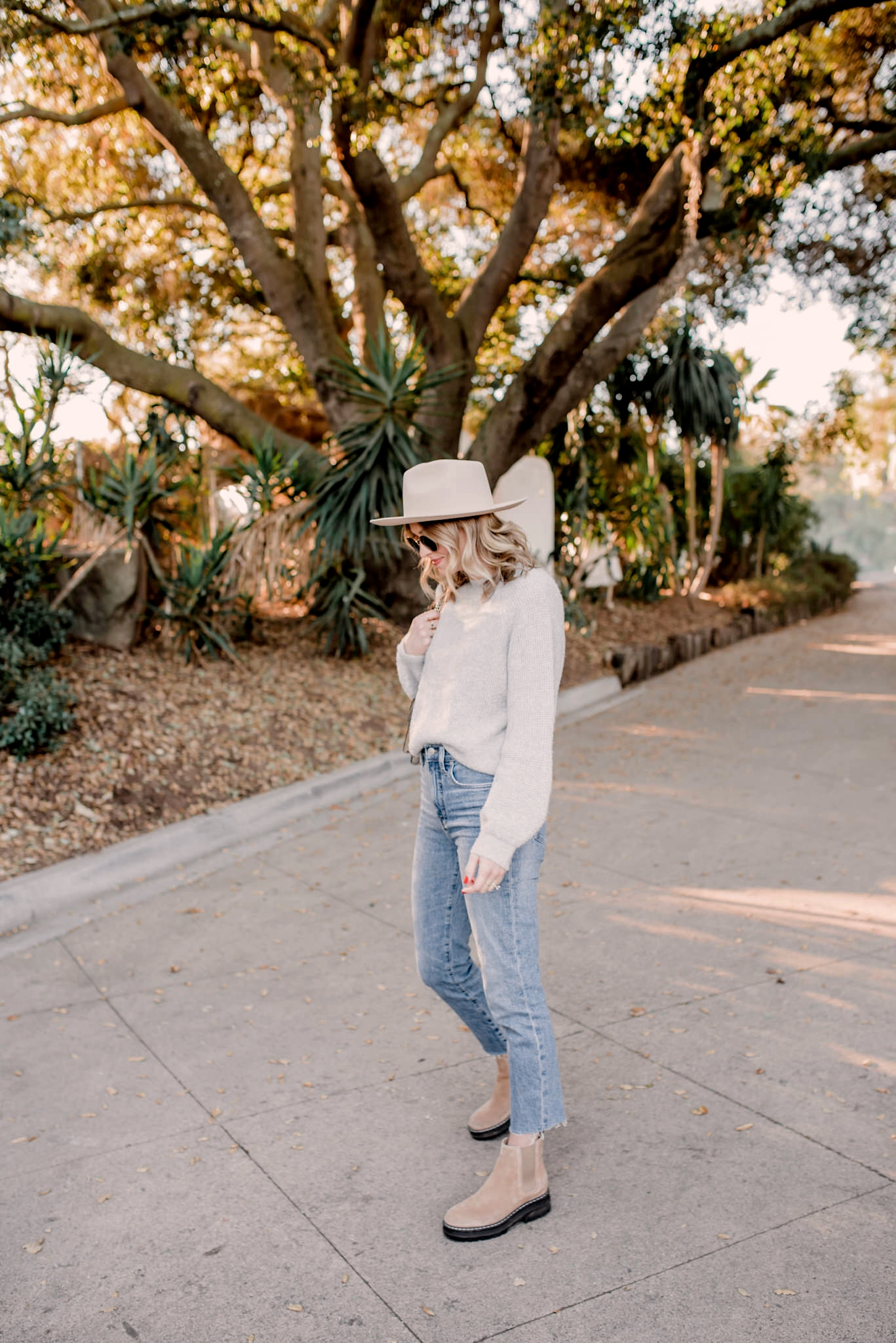 top 10 items of 2020 |Top Items by popular San Diego fashion blog, Navy Grace: image of a woman wearing a grey sweater, tan Gigi Pip fedora, jeans, and tan suede ankle boots.