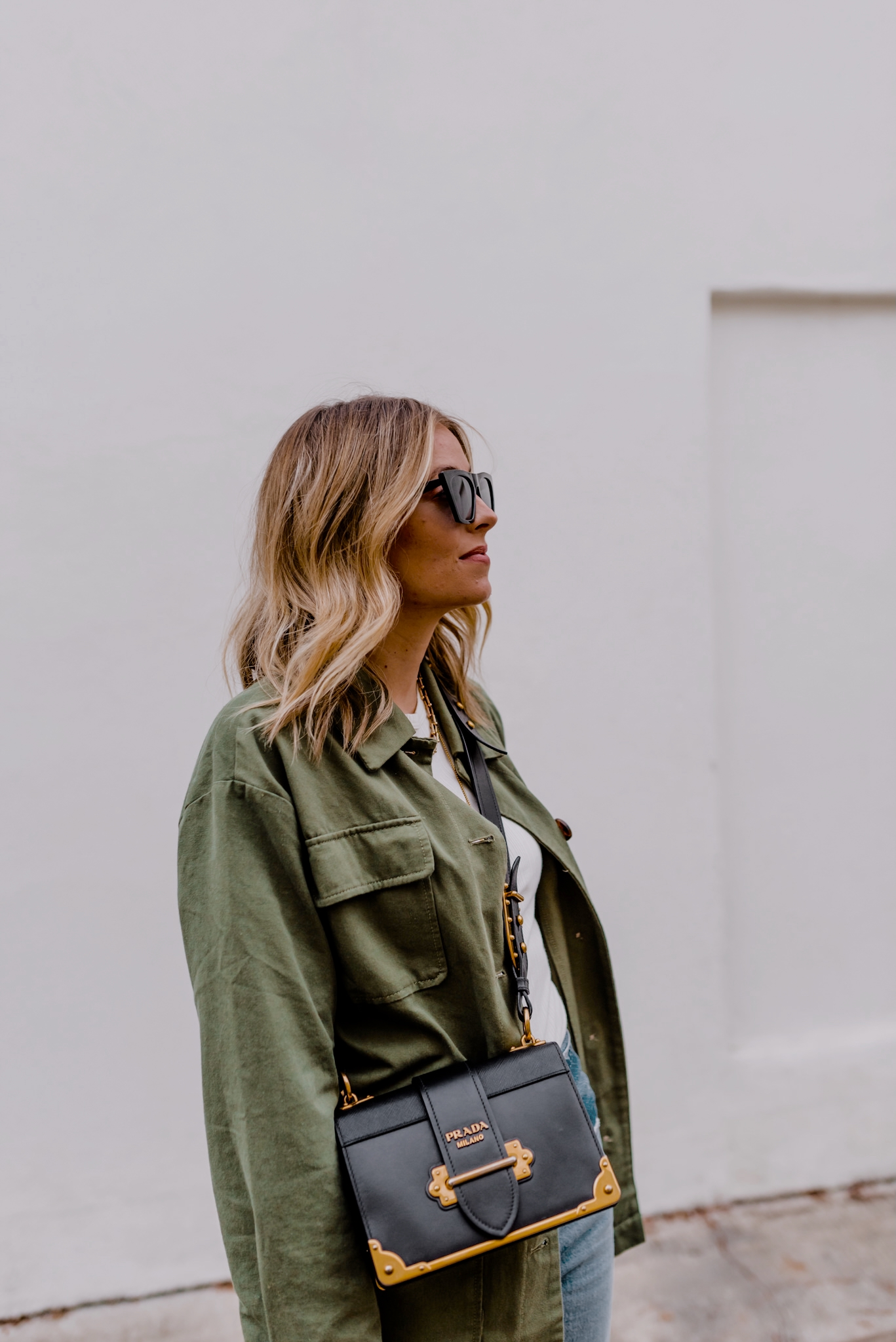 latest amazon buys |Amazon Buys by popular San Diego life and style blog, Navy Grace: image of a woman wearing a green utility shirt, white t-shirt, jeans, and a Prada purse.