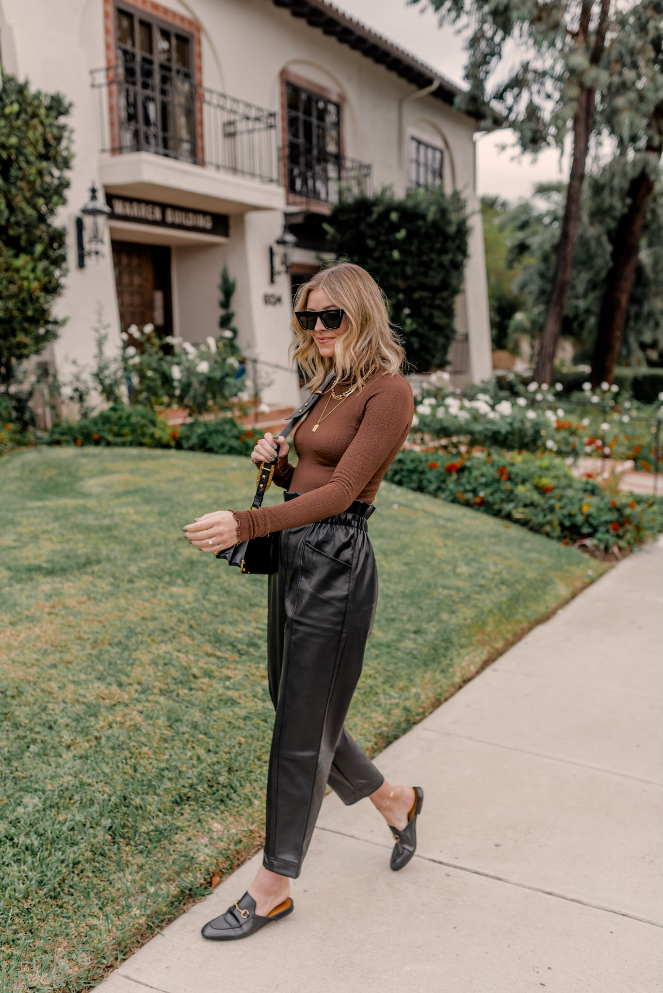 latest amazon buys | Amazon Buys by popular San Diego life and style blog, Navy Grace: image of a woman walking outside and wearing a brown mock neck body suit, black faux leather paper bag pants, and black slide mules.