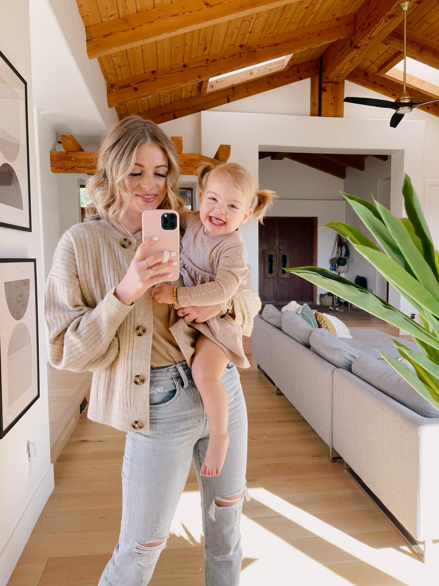 HM FINDS UNDER $100 |H&M Finds by popular San Diego fashion blog, Navy Grace: image of a woman standing in her living room and wearing a tan color t-shirt, tan button up cardigan, and light wash denim.