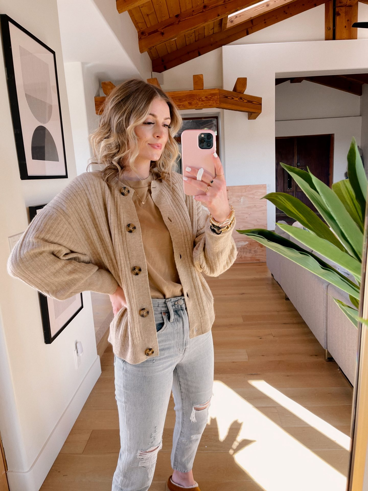 HM FINDS UNDER $100 | H&M Finds by popular San Diego fashion blog, Navy Grace: image of a woman standing in her living room and wearing a tan color t-shirt, tan button up cardigan, and light wash denim.