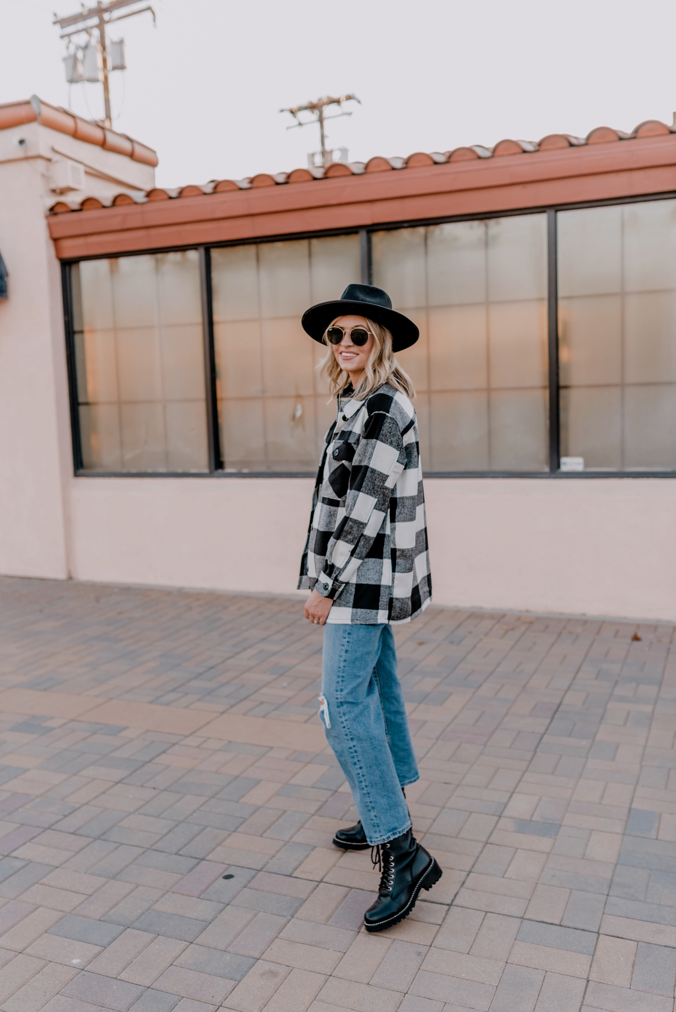 Top Looks of 2020 |Top Looks by San Diego fashion blog, Navy Grace: image of a woman wearing a black and white buffalo plaid jacket, black wide brim felt hat, distressed denim, and black combat boots.