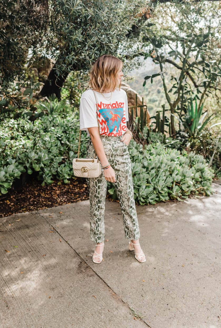 Top Looks of 2020 |Top Looks by San Diego fashion blog, Navy Grace: image of a woman wearing a Wrangler shirt, green snake skin print pants, cream colored block heel sandals, and a Gucci bag.