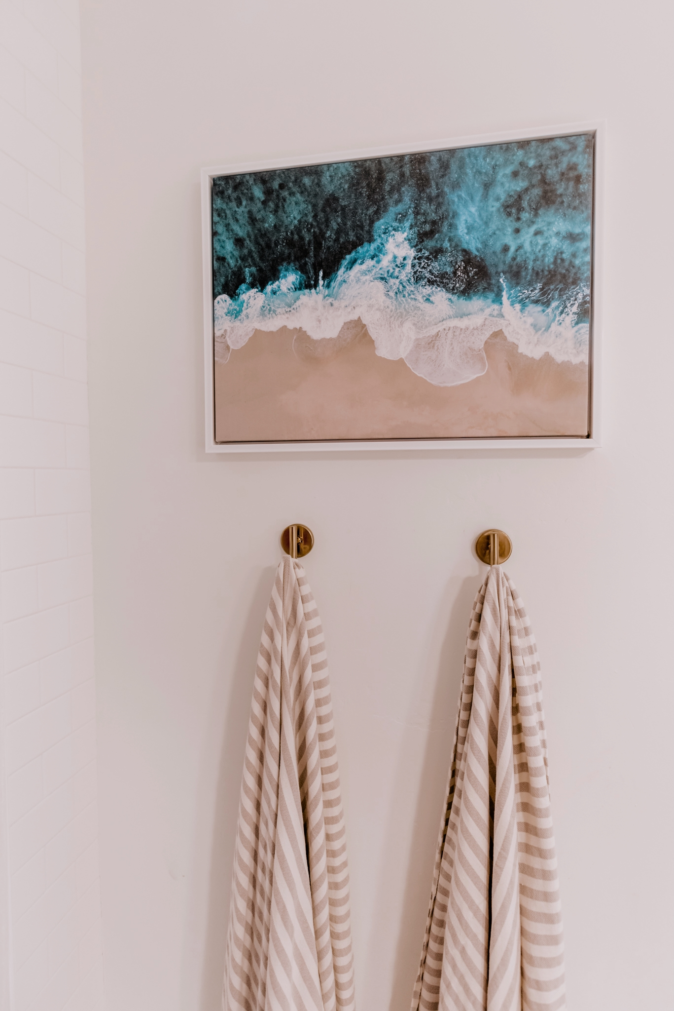 bathroom with a framed image of the beach and hanging towels