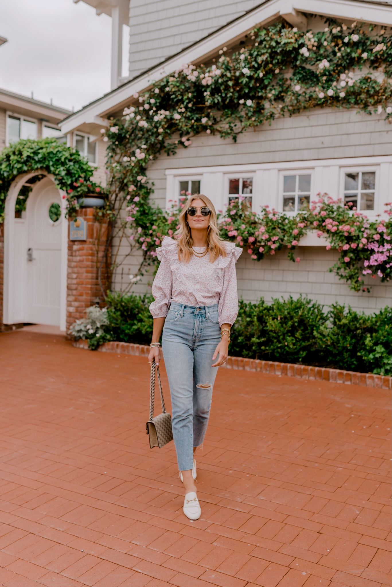 woman walking and wearing jeans and ruffle top