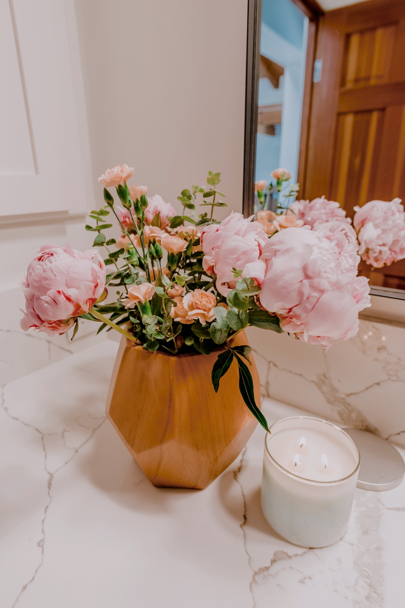 pink flowers on a vase and candle for a collage of Decor Essentials for Hosting Guests